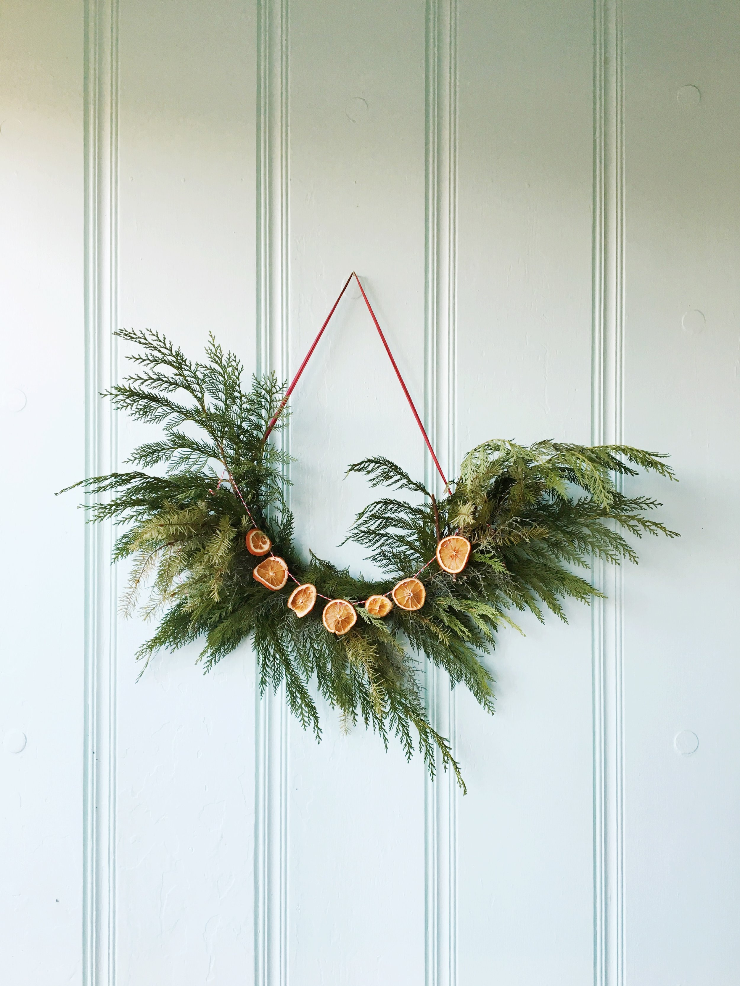 Ashley Daly picked up a beauty of a wreath from  Ever Something  and hung it against her seafoam green house. She also spiced it up a bit with dried orange garland. Oh yeah!