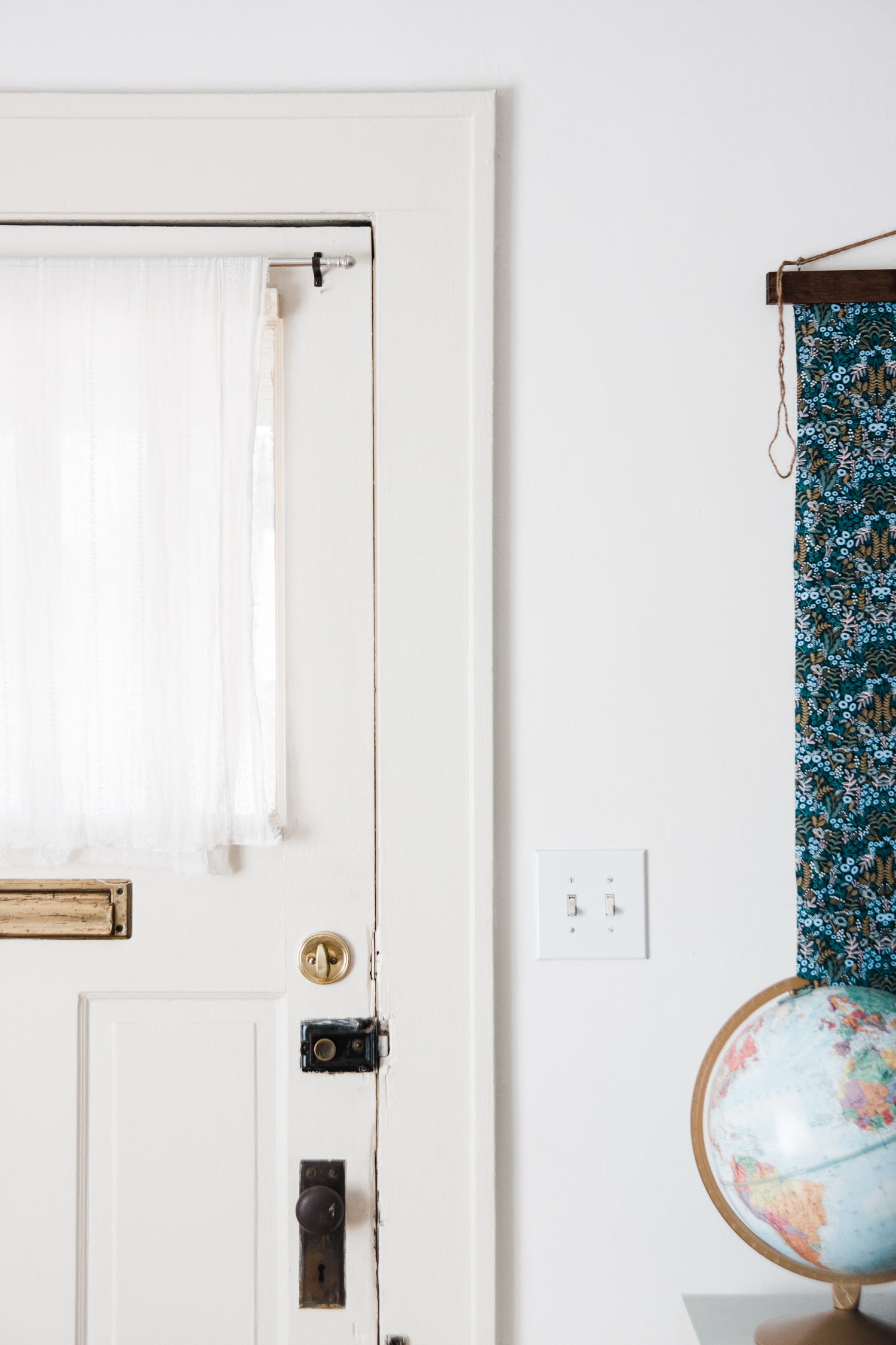Emily draped a simple vintage scarf over the window of her front door for privacy.