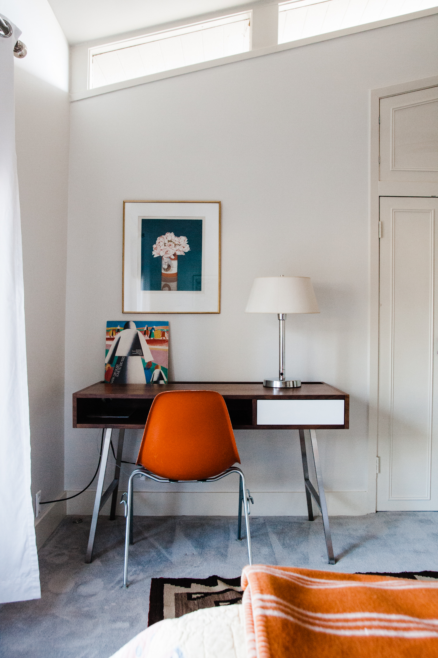 The orange vintage chair brought over the warm hues from the bed and gallery wall on the opposite side of the room.