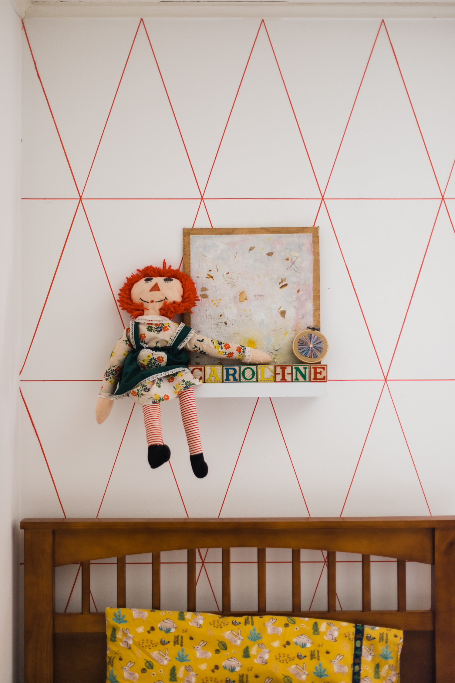 I mounted shelves over each of the beds and created little vignettes on each. For Caroline, vintage blocks spelling her name, an abstract painting given to us by a friend for our wedding and a Raggedy Ann doll a waitress made for me when I was a baby in the 80s.