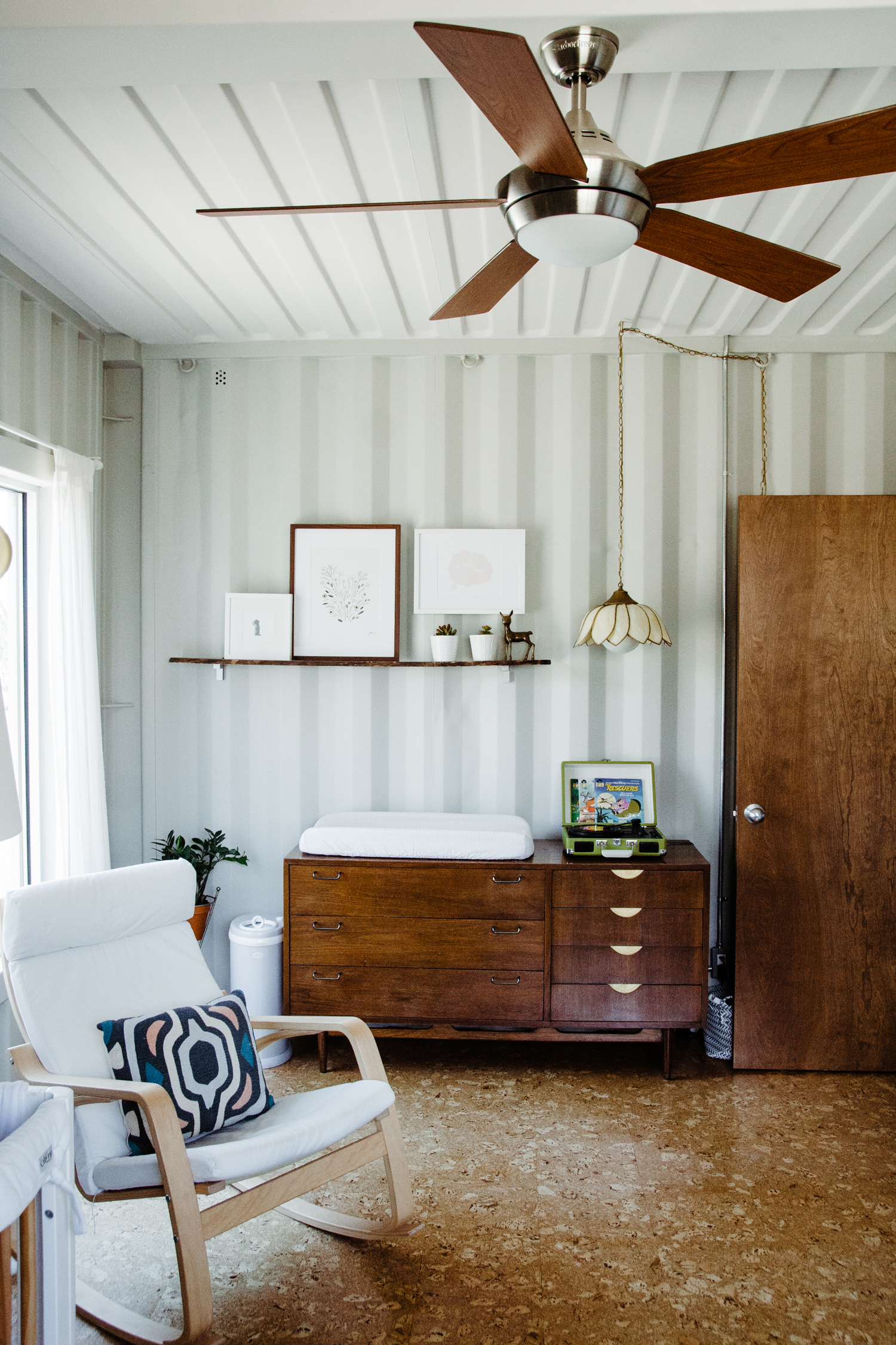 Hannah Bright used both white and dark wood frames in her daughter's room   . All of the frames are streamlined, simple, and call out to other wood and white objects in the room (white crib, wooden dresser, white rug, etc.).
