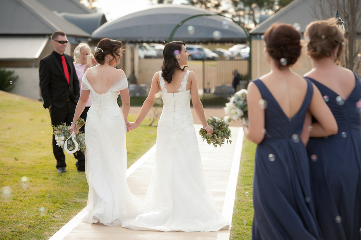 brides walk down the aisle together after their commitment ceremony