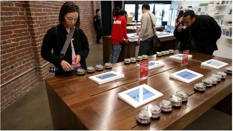 Denise Nugent of Los Angeles looks over flower strains of marijuana at MedMen, a marijuana store in L.A. (Gary Coronado / Los Angeles Times)