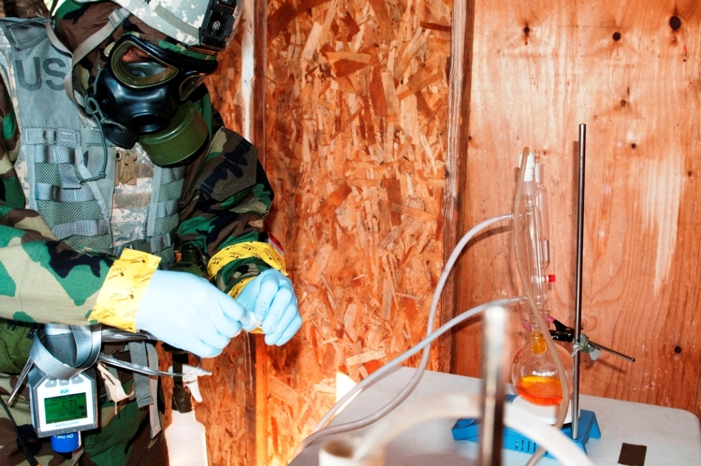 Warrant Officer Christopher Dawson, 9th Chemical Company, gathers simulation samples during training from a site set up as a suspected chemical weapons lab. Operation Rolling Thunder, Oct. 15-17, provided the 110th Chemical Battalion an experience for soldiers trained in tech escort missions to put their sample-gathering skills to the test. Photo by SGT Mark Miranda, 5th Mobile Public Affairs Detachment. Public Domain.