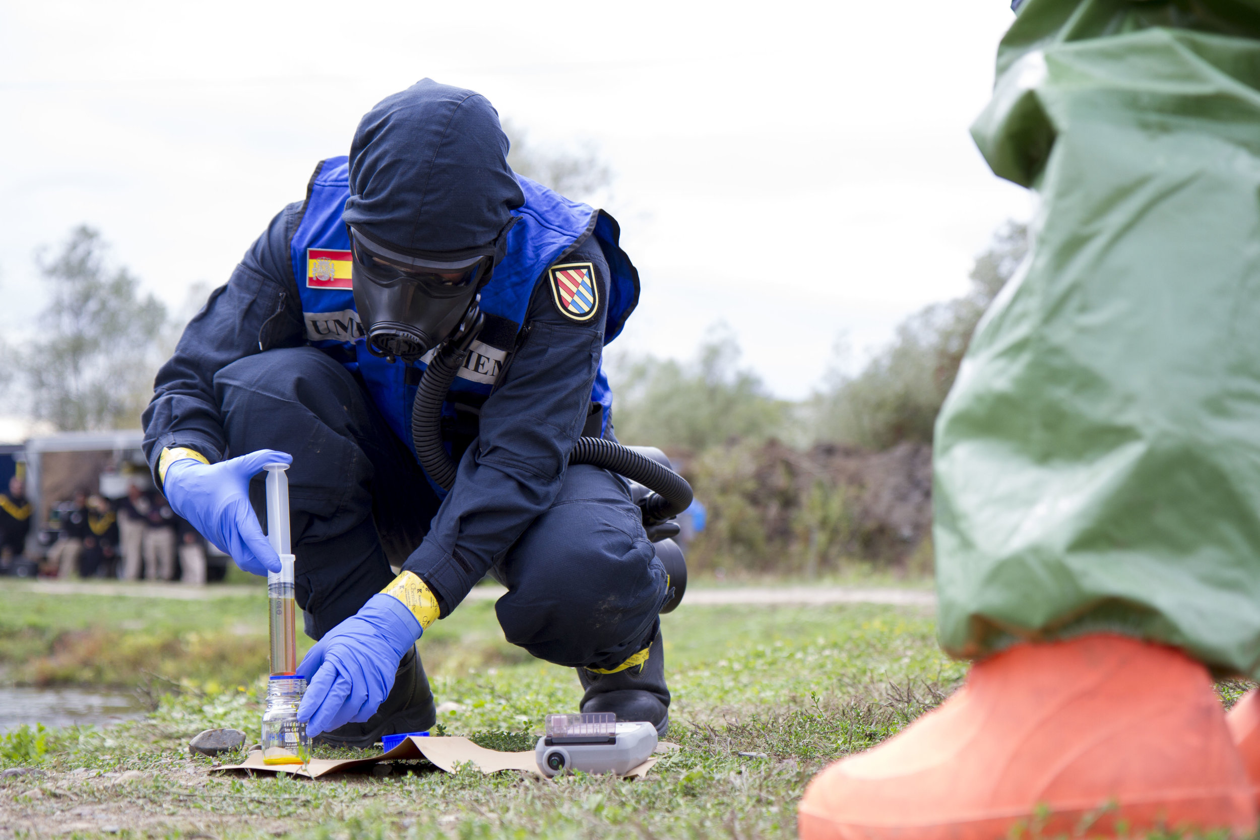 """Maline, Bosnia-Herzegovina (27 September 2017): A Spanish CBRN Specialist conducts field sampling and testing during a chemical spill training event at the Euro-Atlantic Disaster Response Coordination Centre (EADRCC) """"Bosnia-Hercegovina 2017"""" consequence management exercise. Note the APR with PAPR and impregnated suit with nitrile gloves, a slightly modified Level C/MOPP 4. (Source: DVIDSHub.net, Public Domain, US Army Reserve Photo taken by Major Jeku Arce, 221st Public Affairs Detachment)"""