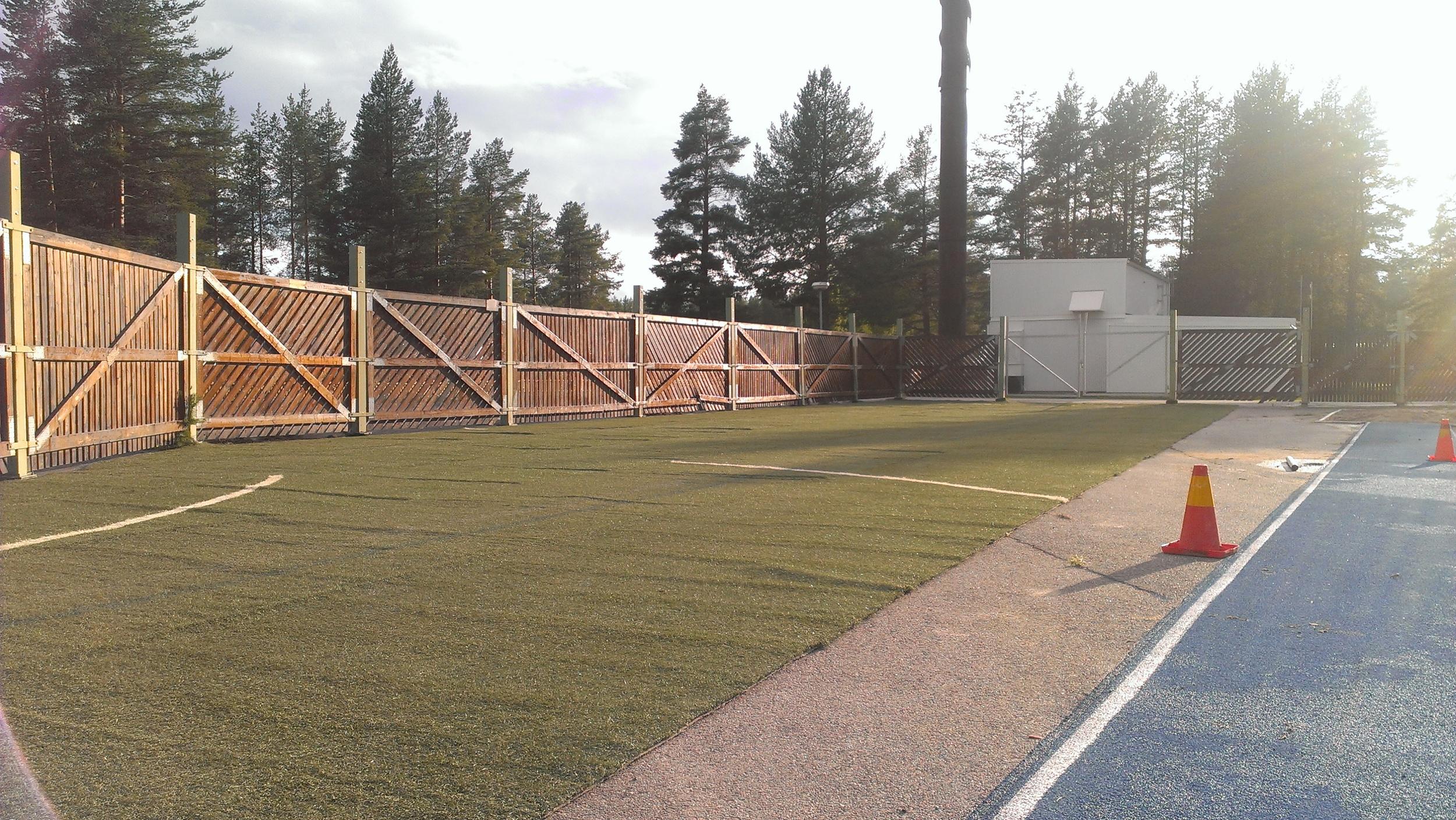 Konstgräsyta för uppvärmning med skottramp för ishockey.