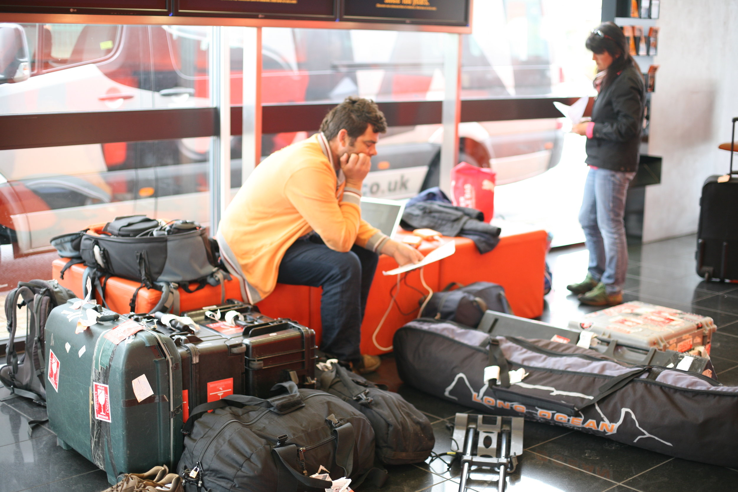 DOP Peter Rudden and I waiting for the paperwork at the hired car depot near Heathrow with gear. The surfboard bag contained tripods and dung-smeared sticks for the shoot, luckily undetected as we passed through the airport 2013.