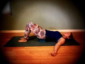 Resting Bridge - Resting bridge pose. Place your feet on the mat and knees in the air. Place a blanket or yoga block under your sacrum. Be cautious with bridge pose if you have any lower back problems.