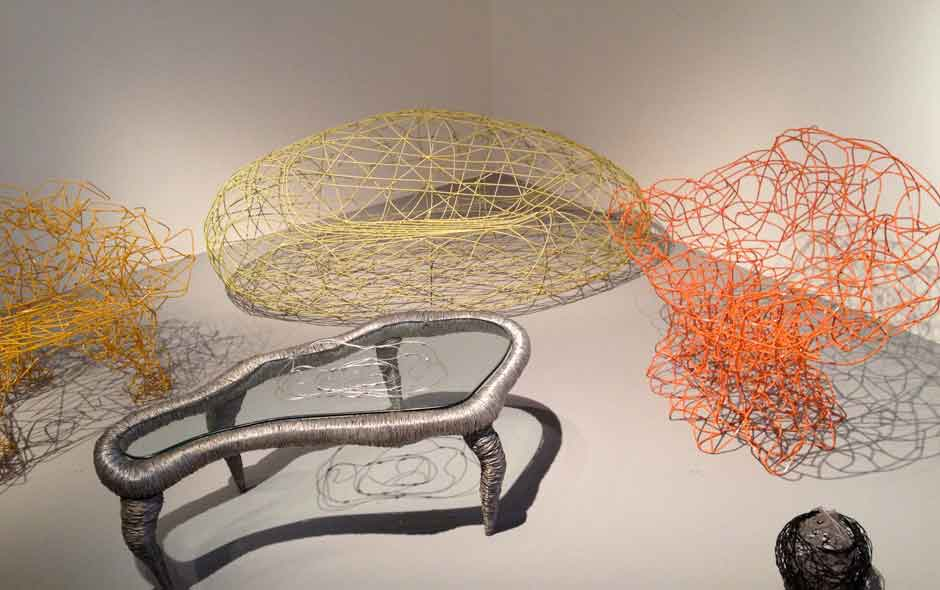 3/4 An experiment with wire, the Corallo armchair by Edra (orange) accompanied by the early prototypes.