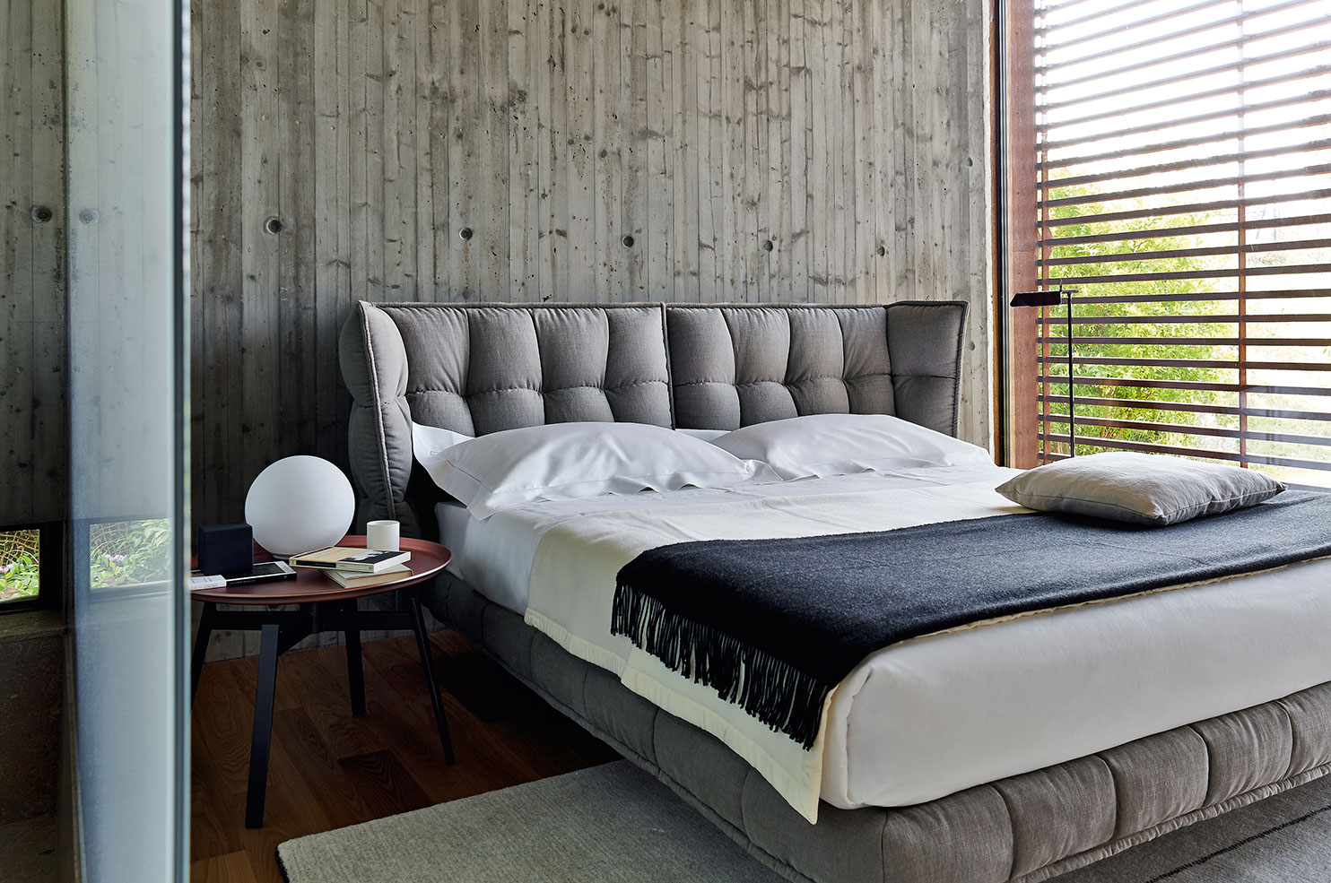 B&B Italia's Husk bed  is a soft touch against this concrete wall. Instead of a conventional bedside table, beside the bed is the  Husk side table .
