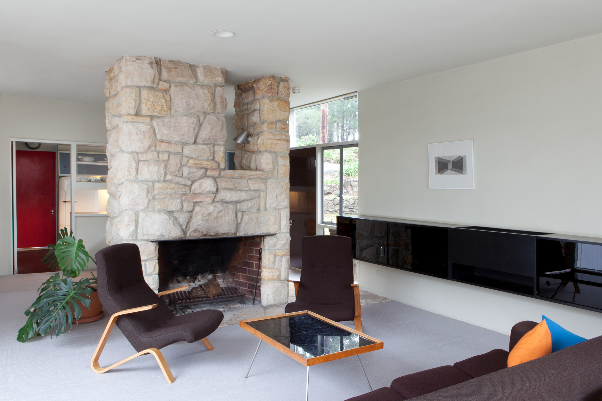 The open plan lounge room featuring the central fireplace and dining area behind. Photograph copyright Jamie North for Sydney Living Museums.