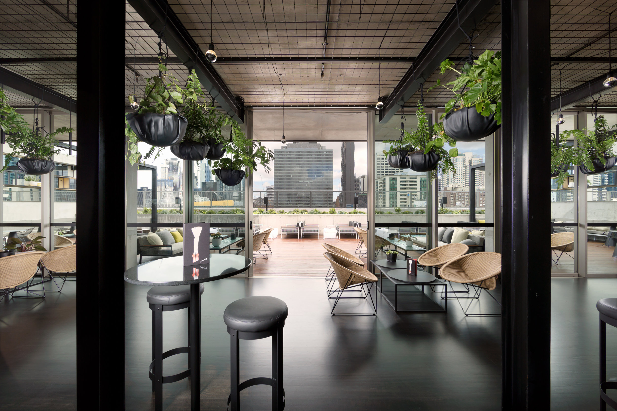 The QT Melbourne with its city views mirrored and transformed with light and plants on the rooftop of the hotel.