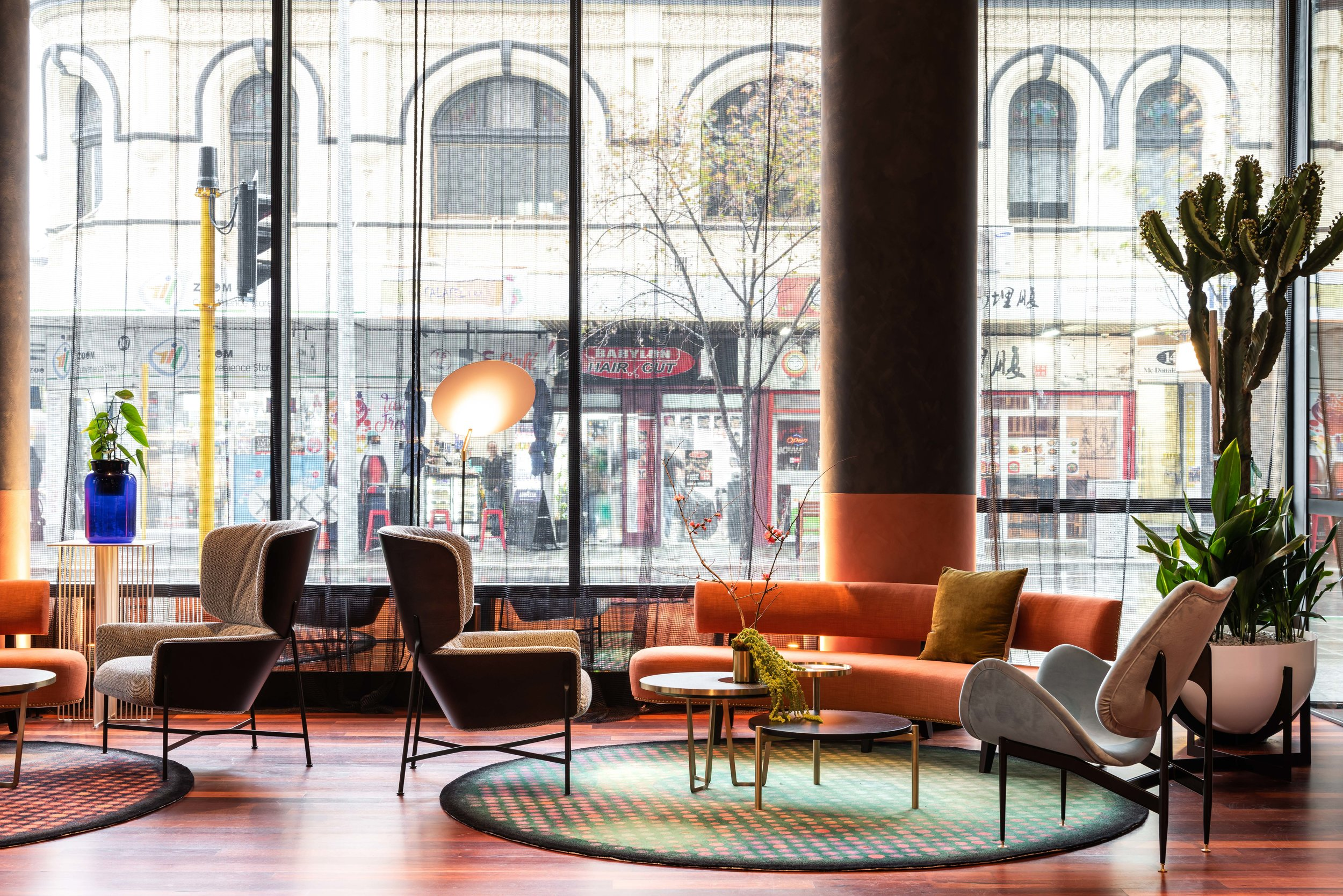 The lobby area of the recently opened QT Perth is a mix of bespoke furniture pieces, the newly released  Caristo Armchair s by SP01, and careful theatrics that expand the space through mirror and large artworks.