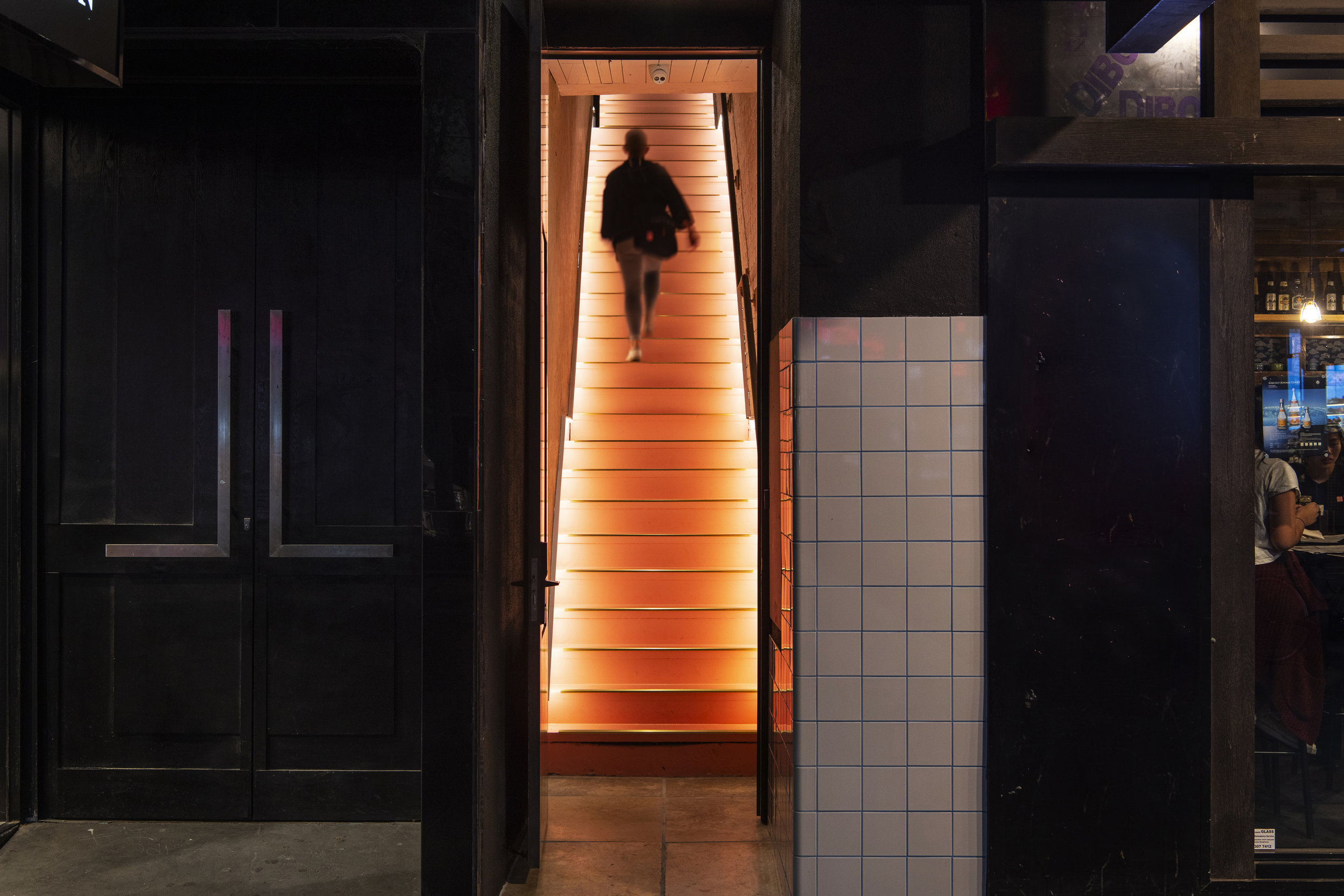 An illuminated staircase transports guests from Cheek upstairs to Peaches. Photo © Pete Dillon