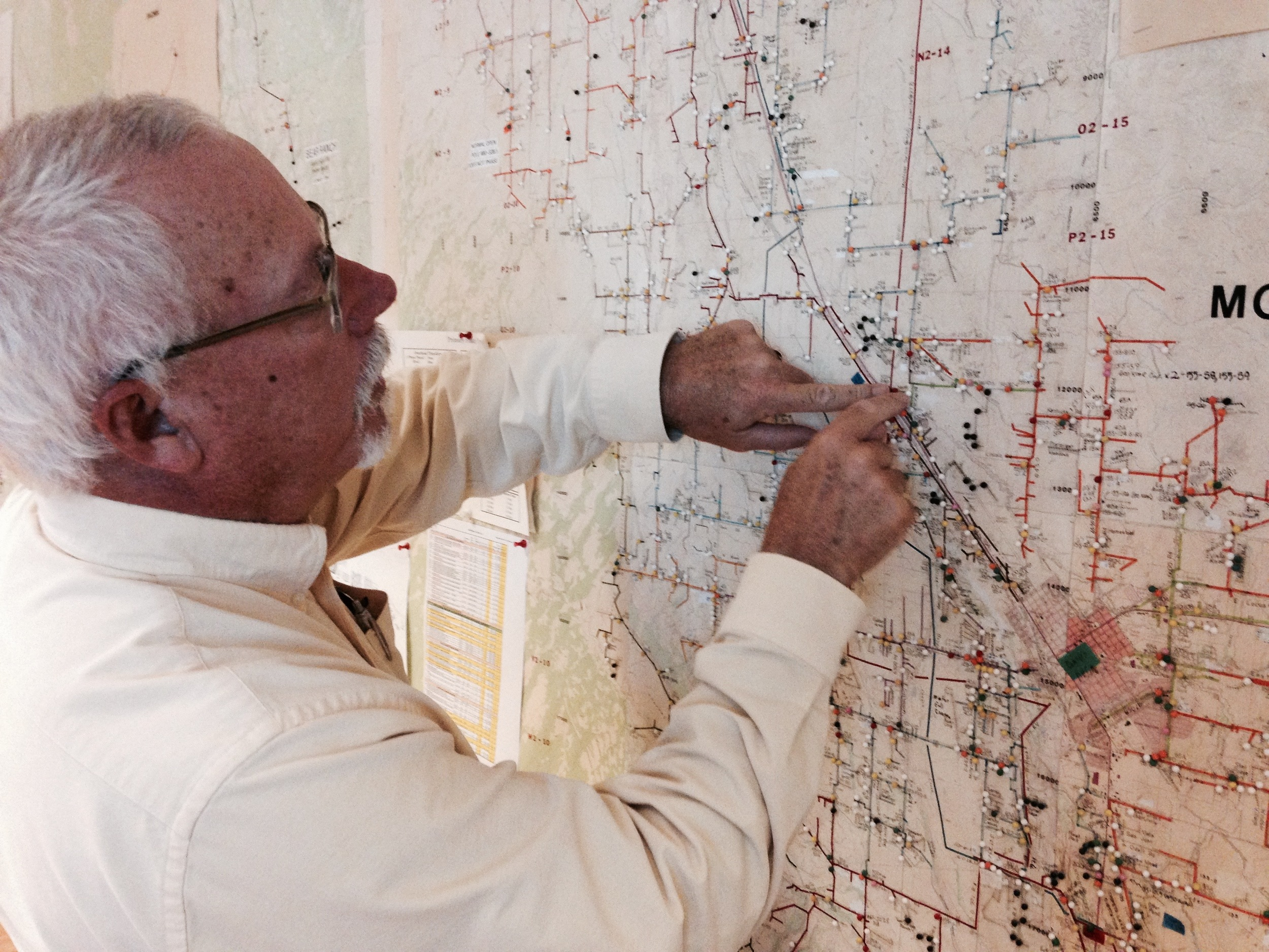 Steve Metheny, of the Delta-Montrose Electric Association, illustrates the utility's back-up to the back-up: a floor to ceiling paper map of their service area and infrastructure. Jordan Wirfs-Brock.