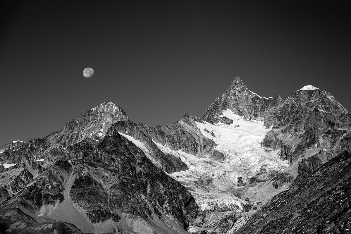 The moon sets during the day over the Pennine Alps in Switzerland