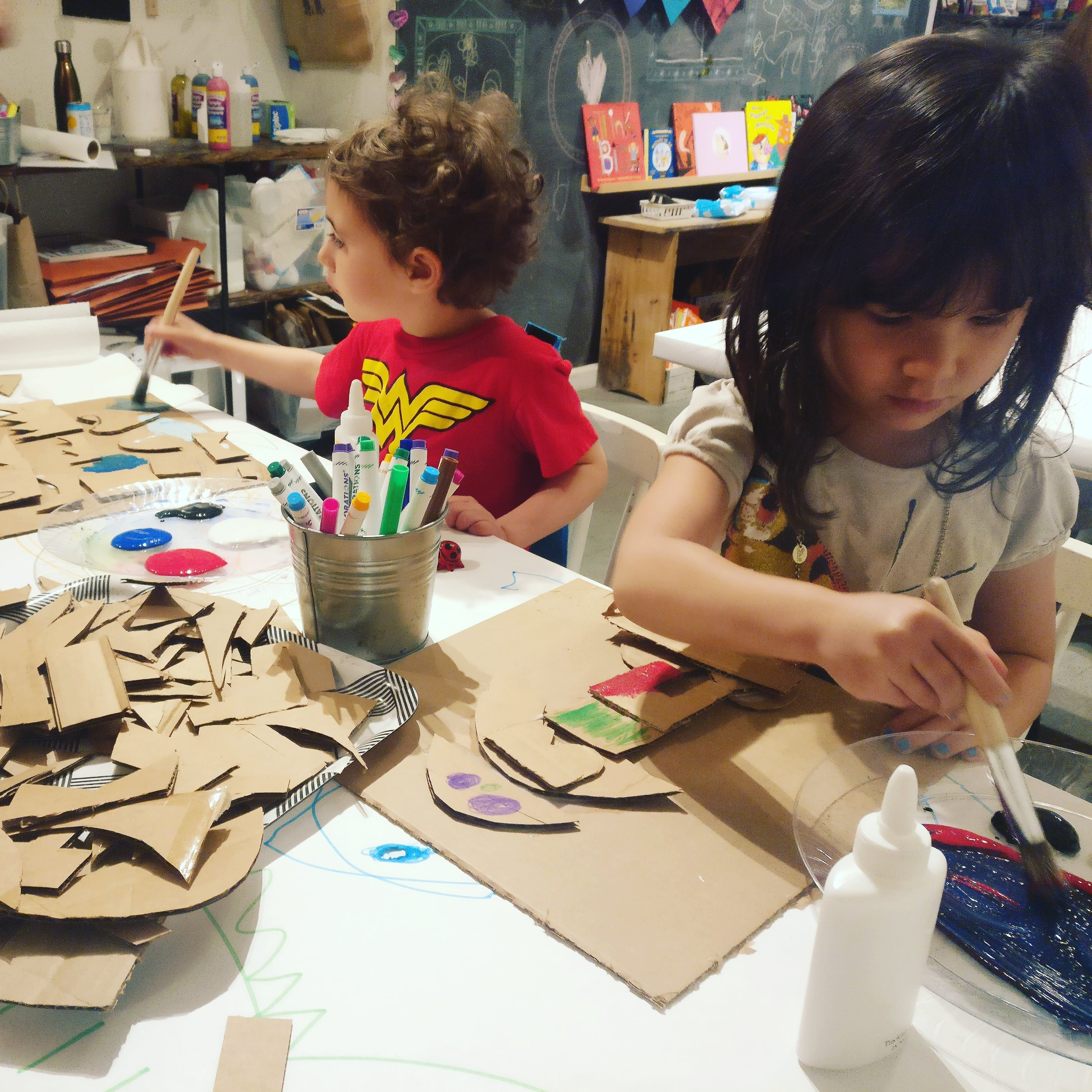 Students making cardboard self portraits.