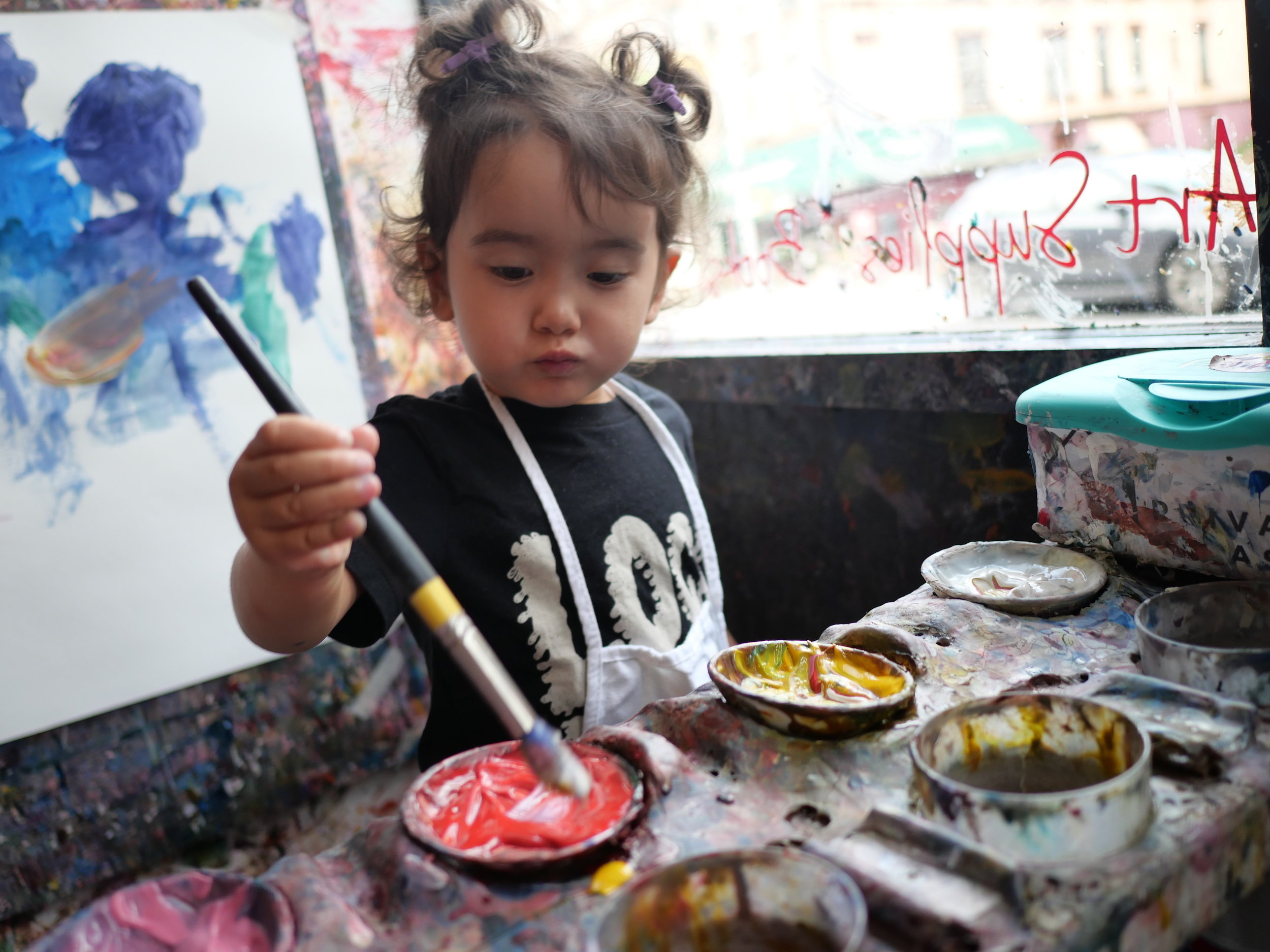 Toddler painting at our painting palette.