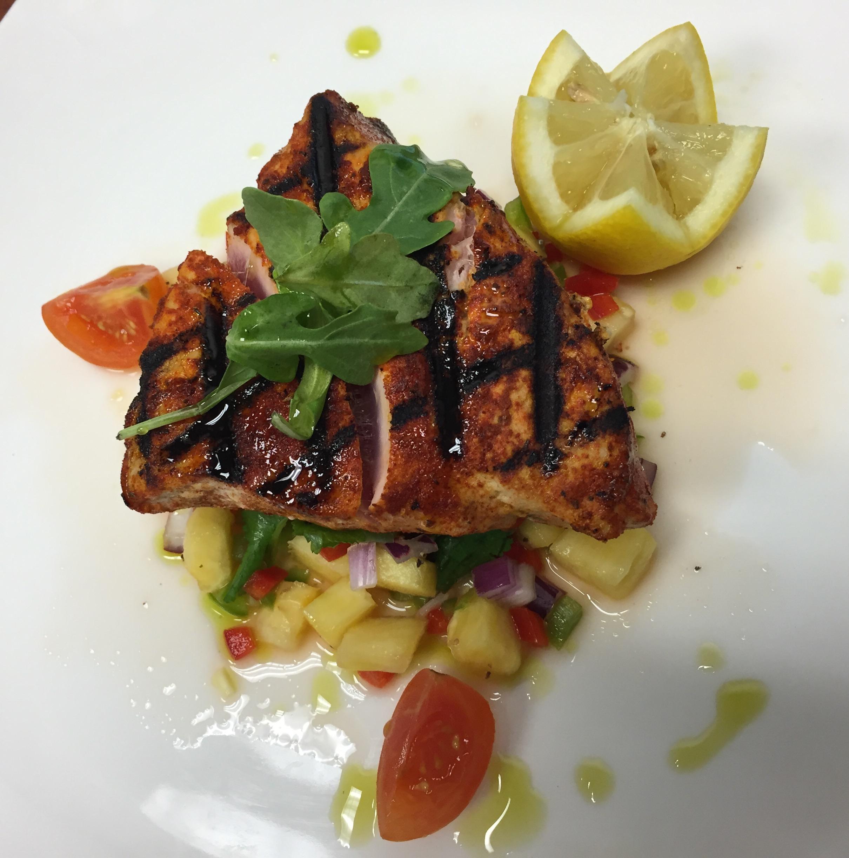 Blackened, seared ahi tuna with fresh, spring pineapple salad. Basil oil and lemo garnish.