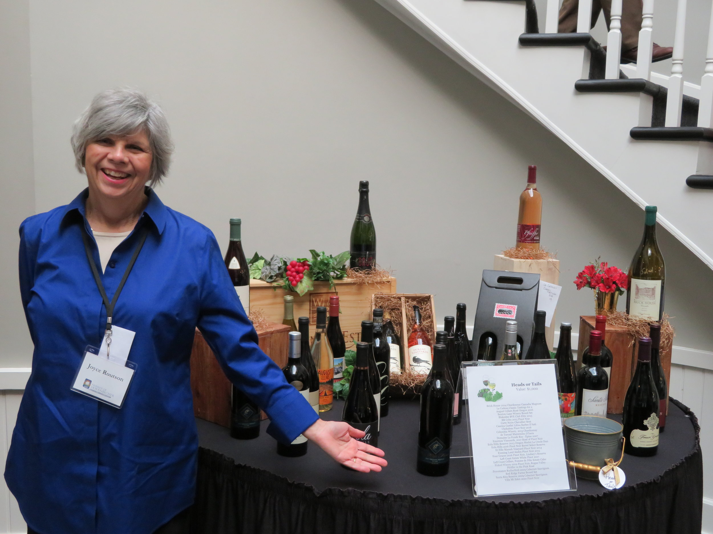 Volunteer Joyce shows off the wine lot.