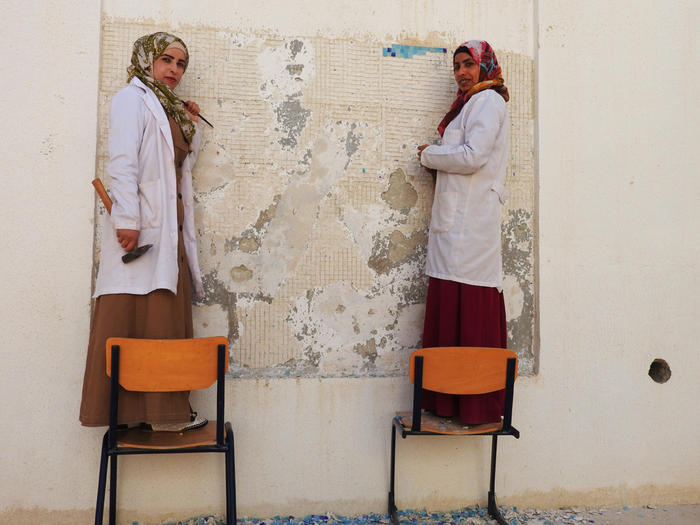 Students at the Madaba Institute prepare a wall for a new mosaic.