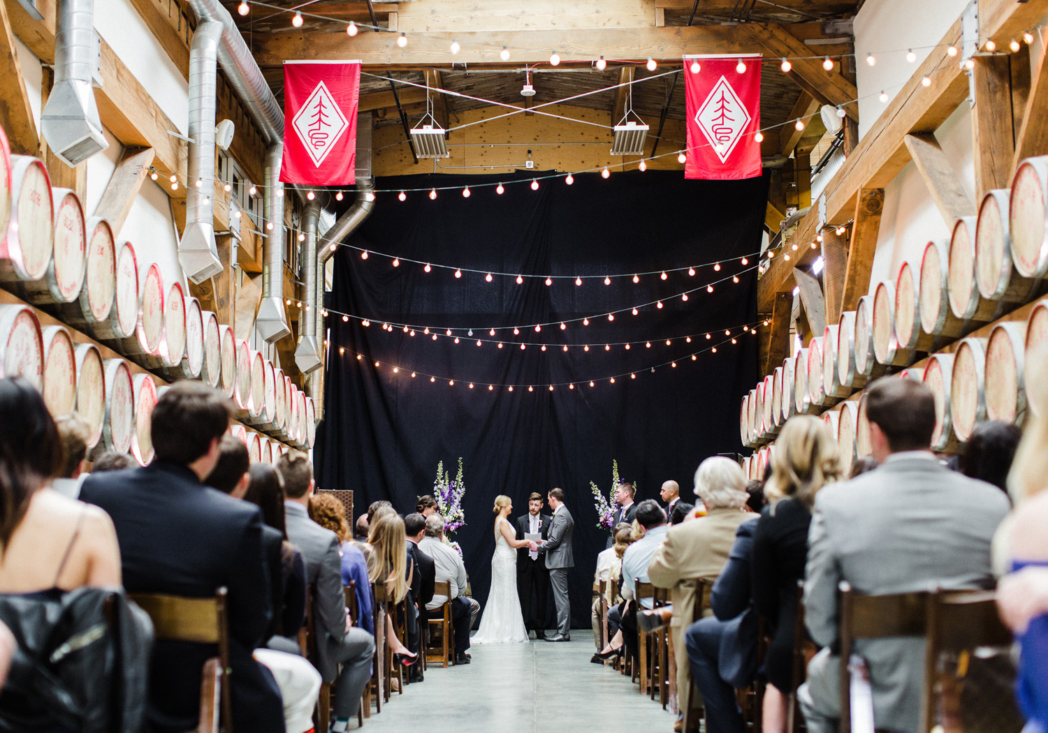 Westland Distillery Indoor Wedding Ceremony Barrel Room by Alexandra Knight Photography Seattle Wedding Photographer
