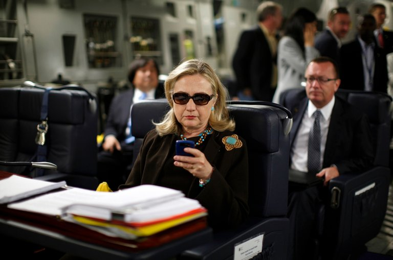 Hillary Clinton, as secretary of state, checking her BlackBerry while on a military plane in 2011. Credit Kevin Lamarque/Reuters, taken from Kristof's  Is Hillary Clinton Dishonest?