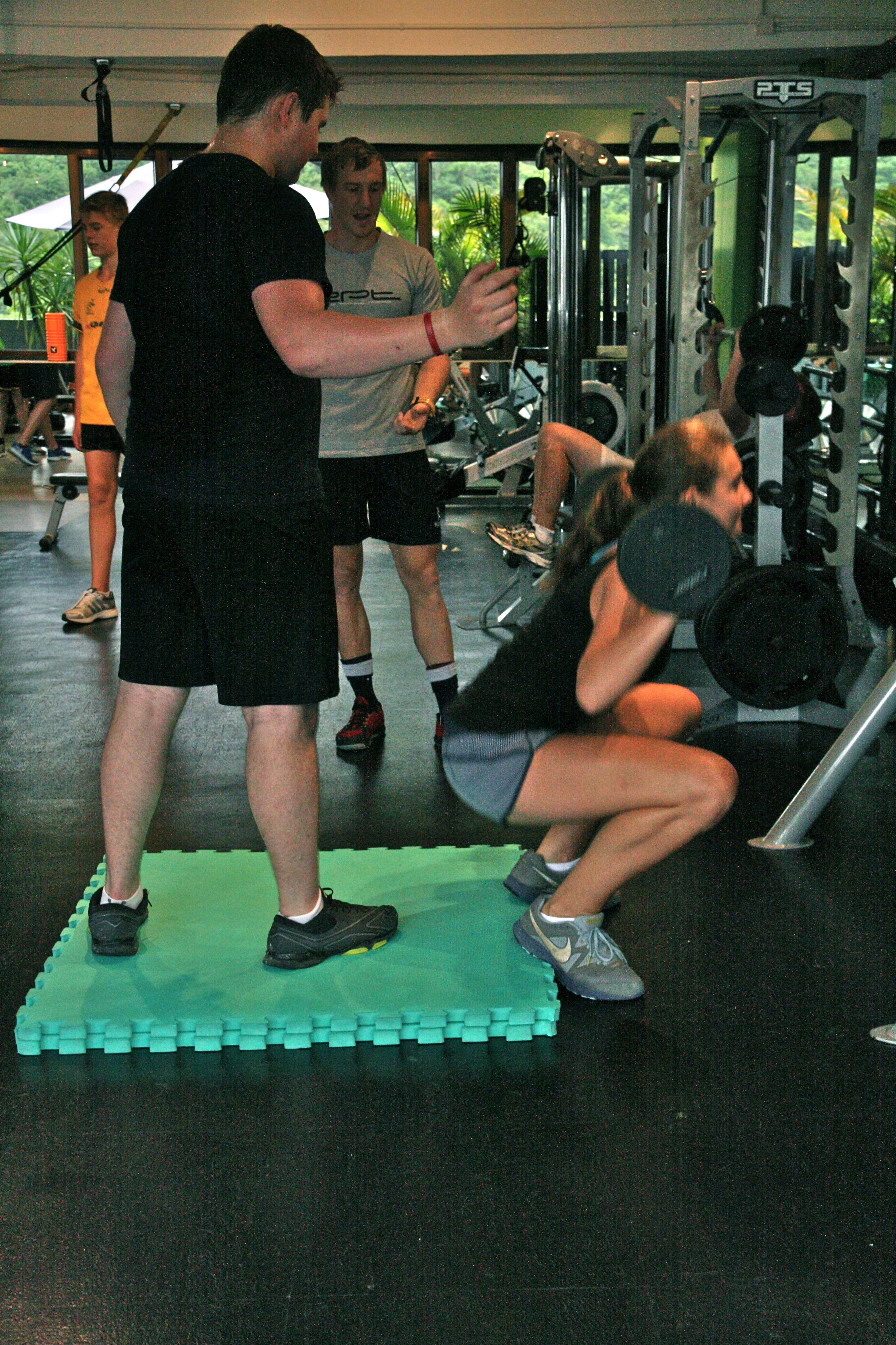 Girl teen deep squatting with trainer watching - side view.jpg