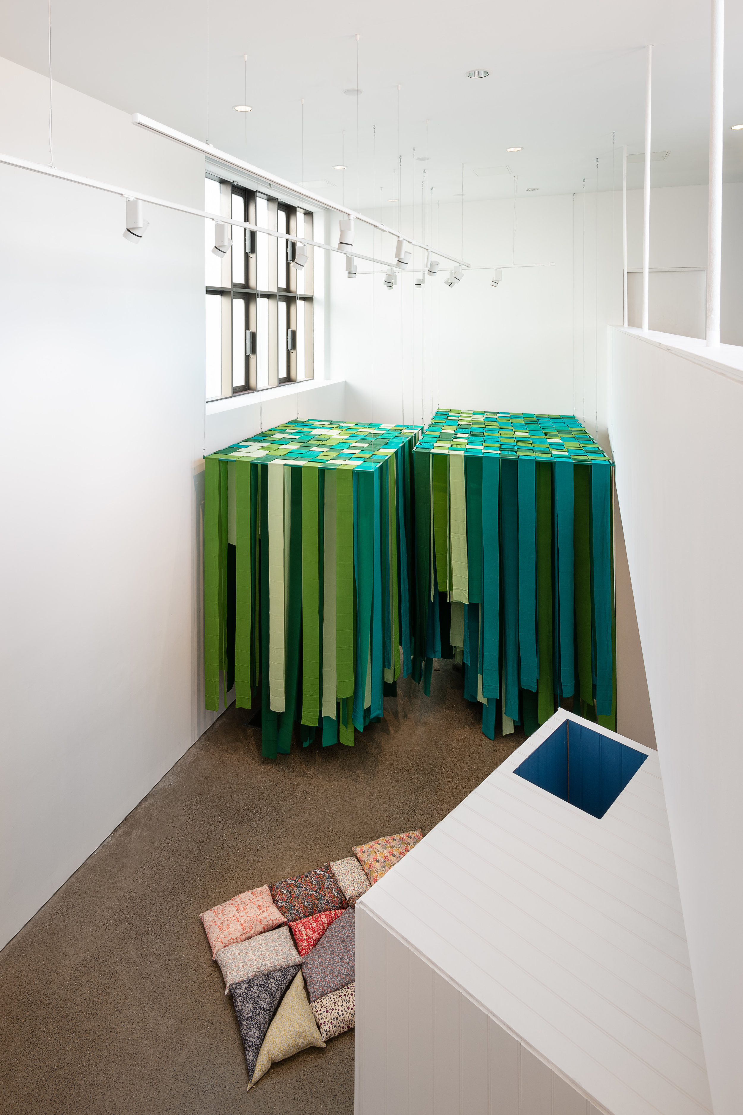 View from balcony Centre -  Mobile Element - Cushions for arranging, and sitting or lying on;  fabric, cushion filler;  Right -  Element 2 (passageway),  painted wood; Background -  Element 1 (green canopy),  powdered steel, silk Caoimhe Kilfeather Photo by Jed Niezgoda