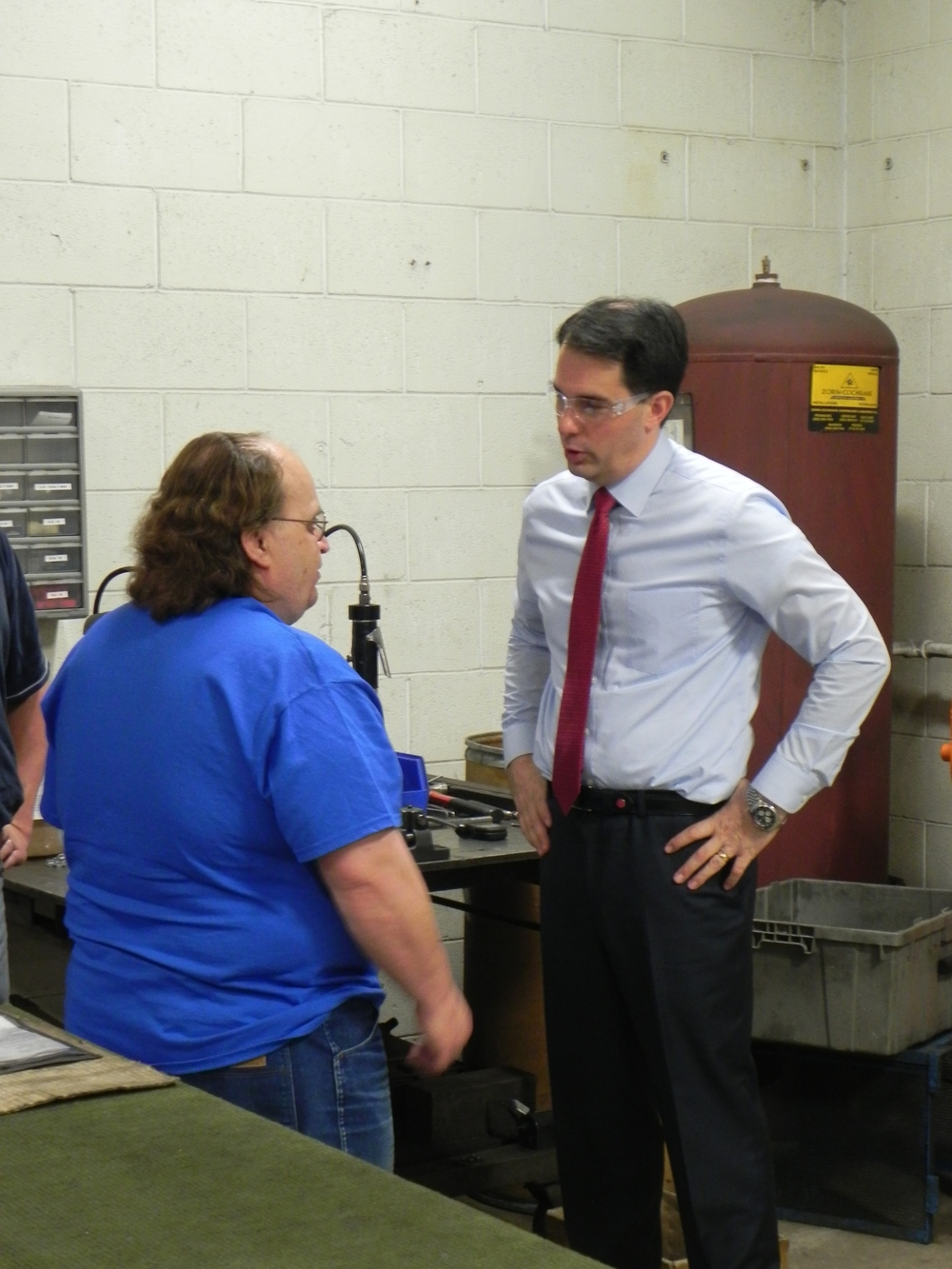 Spencer (pictured left) talking with Governor Scott Walker at his work station.
