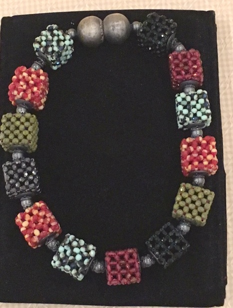 "A Multicolor Three-by-Three Cube Necklace, acquired at the Palm Beach Fine Craft Show in February, 2016 by Myrna L., of the Palm Beach, FL area.     Myrna says:   ""I have worn this necklace so many times and get many wonderful comments. I was in a store in Palm Beach with my niece, and a stranger offered to buy it."""
