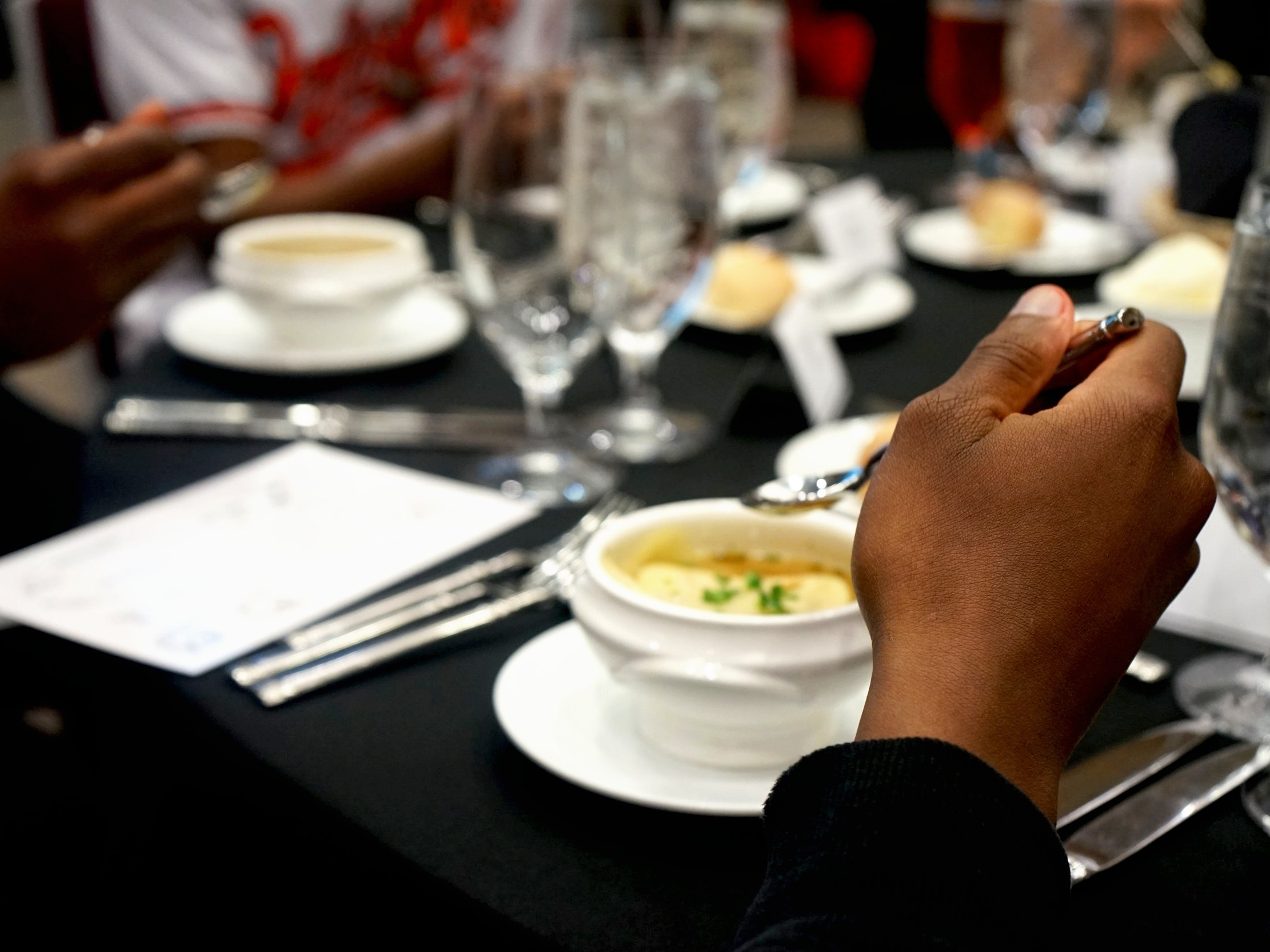 Students exhibit the proper spoon placement during the meal's first course.
