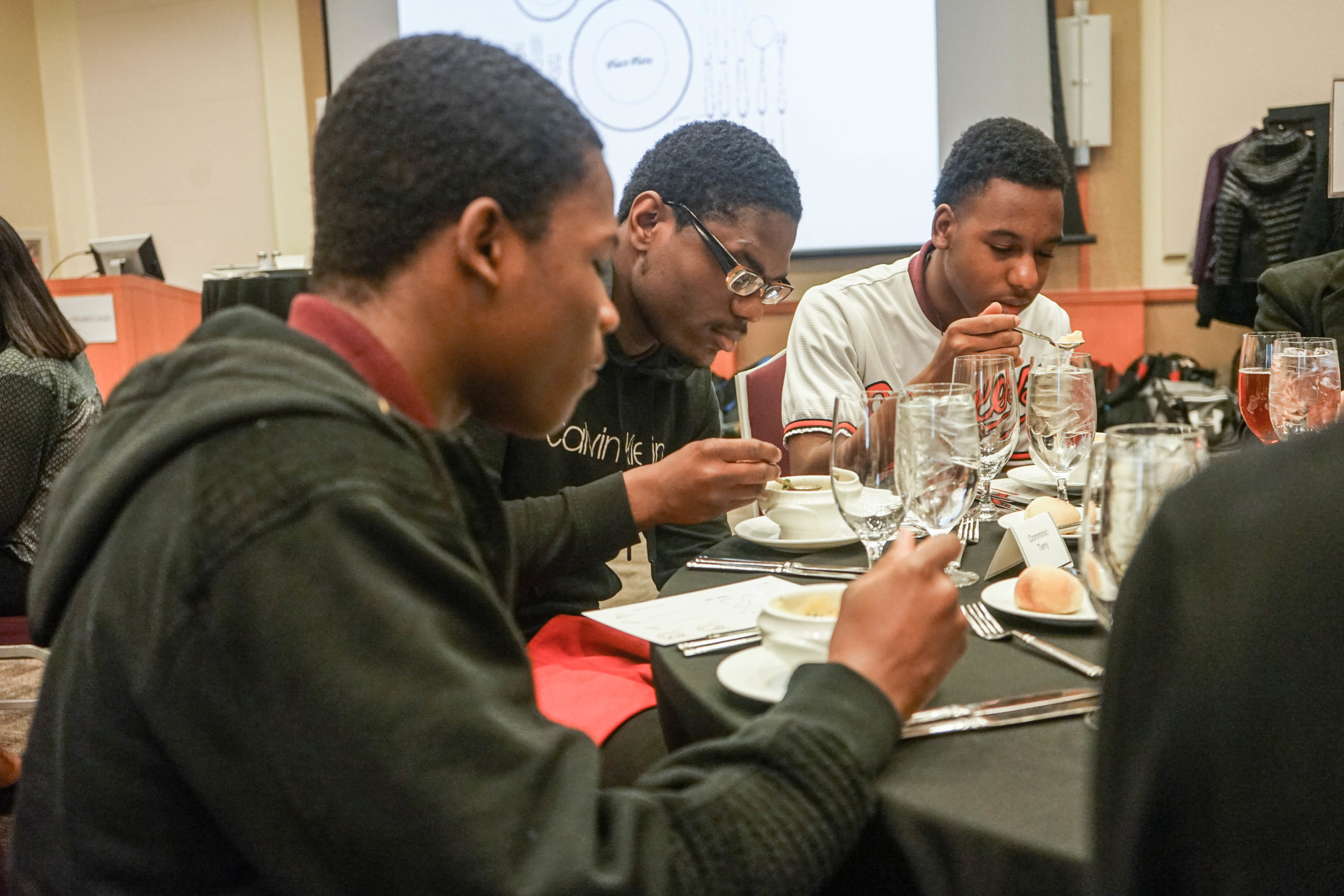 Three students from Renaissance Academy High School cool their soup. French onion soup was the first course of a four-course etiquette dinner at the SMC Campus Center, U of Maryland.