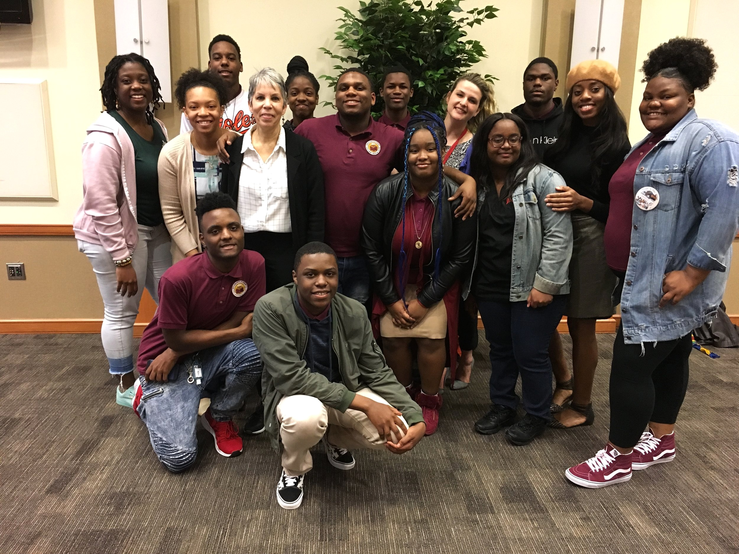 Students from Renaissance Academy High School and staff including Promise Heights College and Career Coordinator, Shirley Green (second to the left) and Promise Heights Director, Bronwyn Mayden (third to the left) gather for a group photo following the etiquette dinner at the University of Maryland, Baltimore Campus Center.