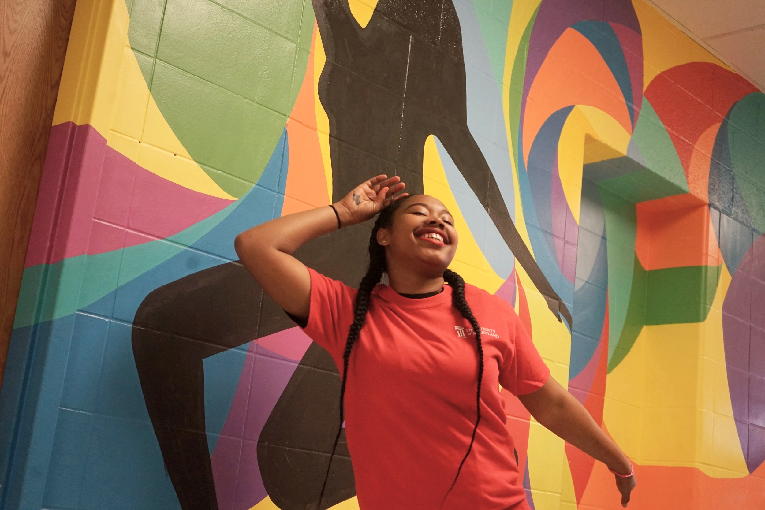 Dyelle Washington, a sophomore at Renaissance Academy strikes a similar pose to the mural she stands in front of and helped to complete.
