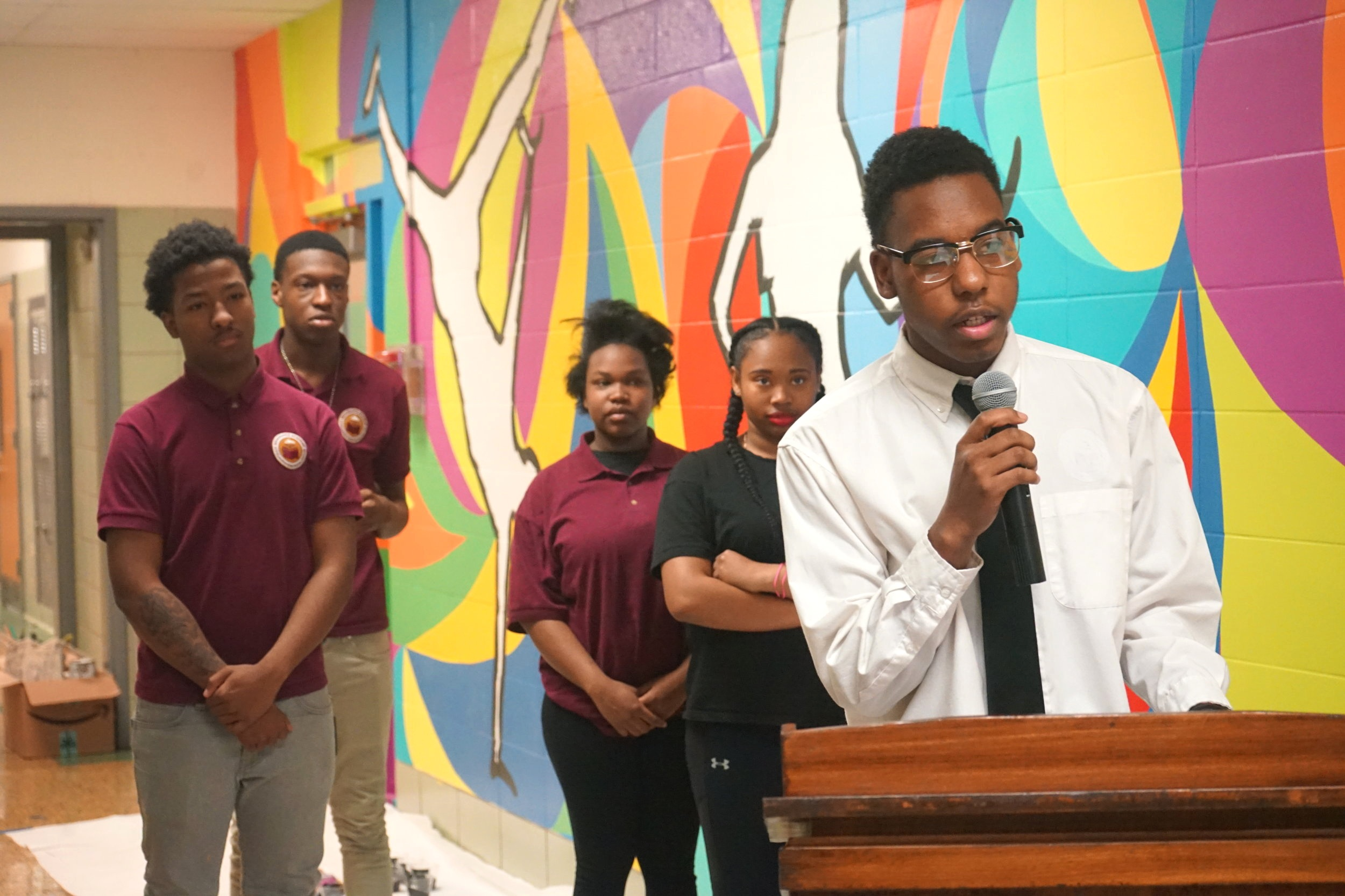With the support of his classmates behind him, Kevin Flemming, a junior at Renaissance Academy delivers his speech to the audience during the mural unveiling.