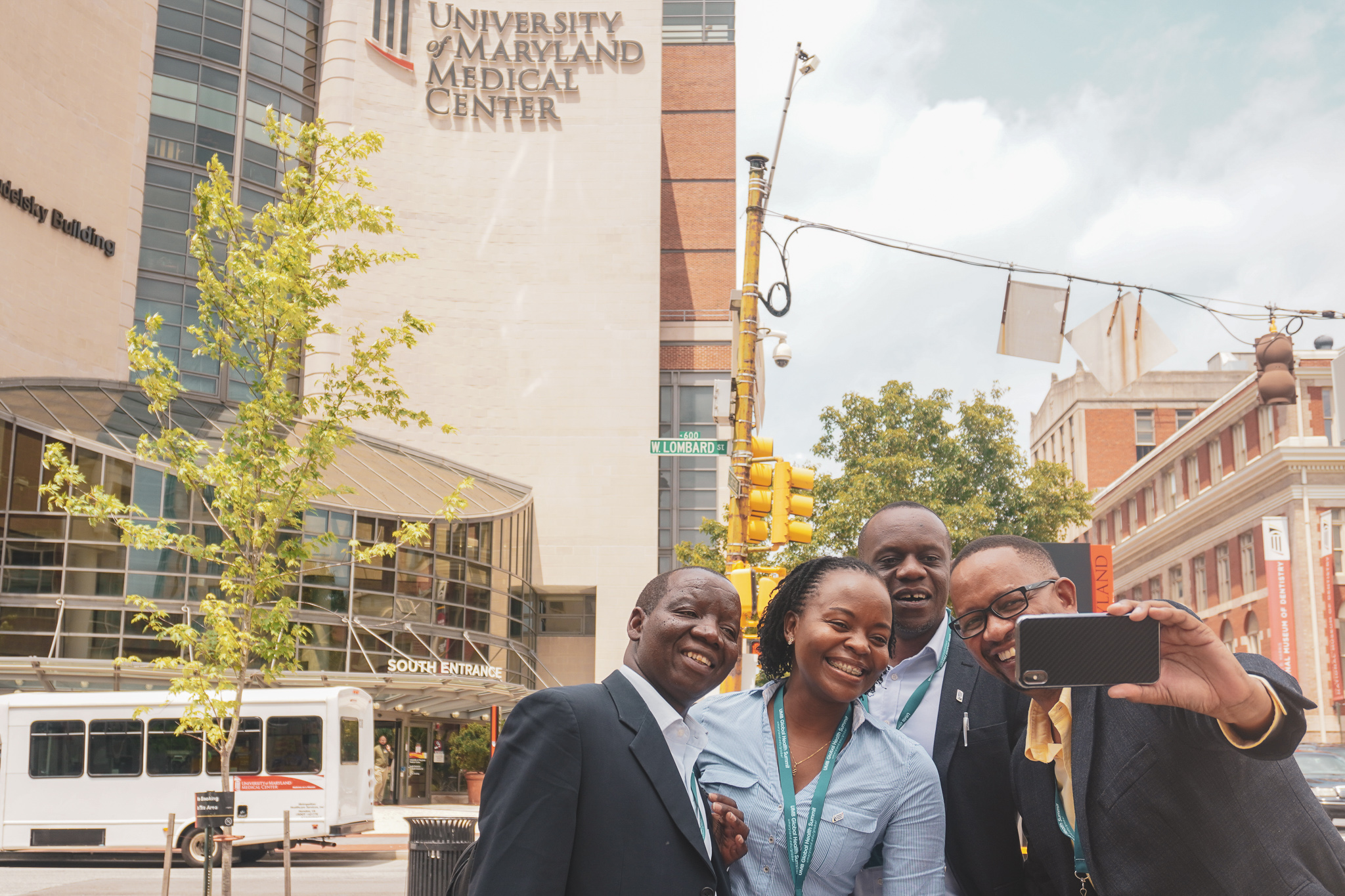 """Photo Caption: After a tour around West Baltimore, four members of the delegation from African countries stop outside the University of Maryland Medical Center for """"selfies"""" and light-hearted smiles."""