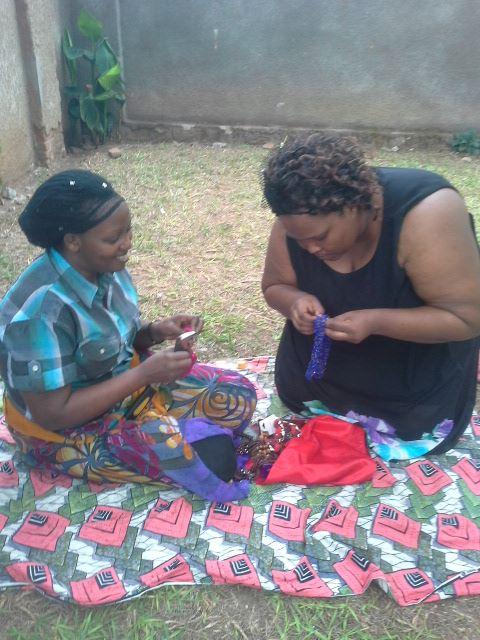 Women in Burundi making beaded necklaces