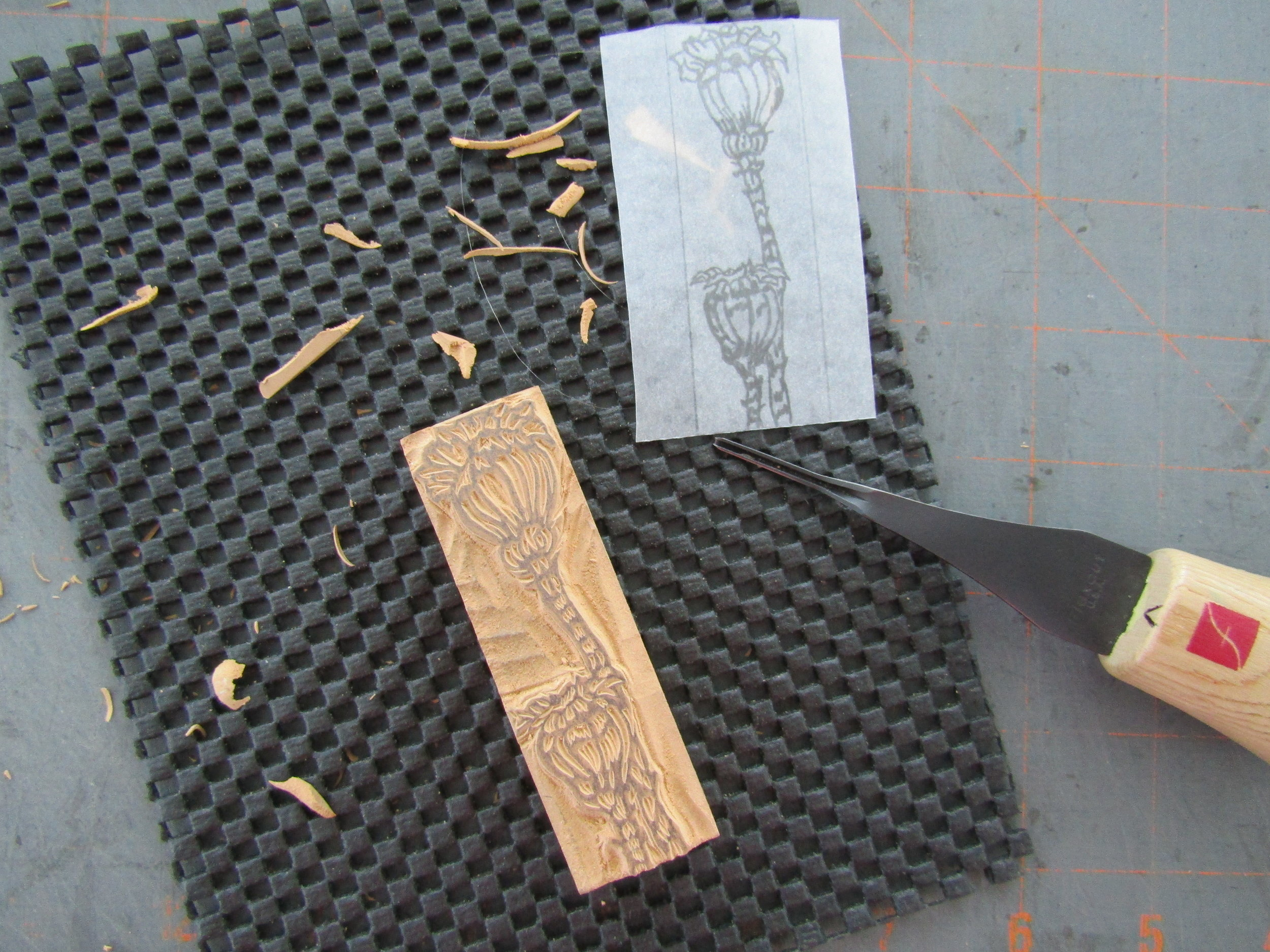 Carving a small block based on the sketch of the poppy pods.