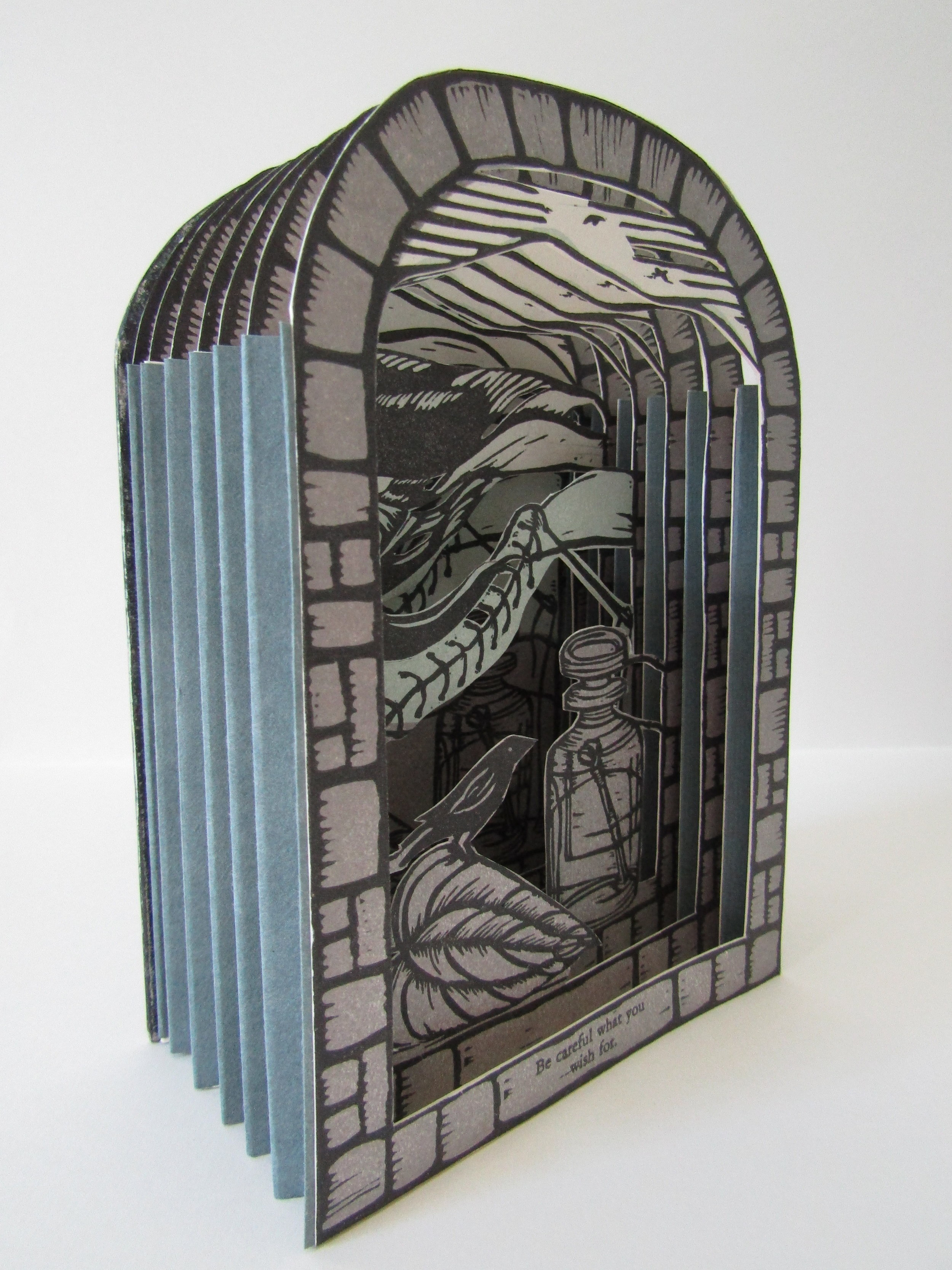 This image shows how the accordion folded papers hold the book together at the sides of the assembled book. This also shows how the pages extend out creating the layered interior pages.