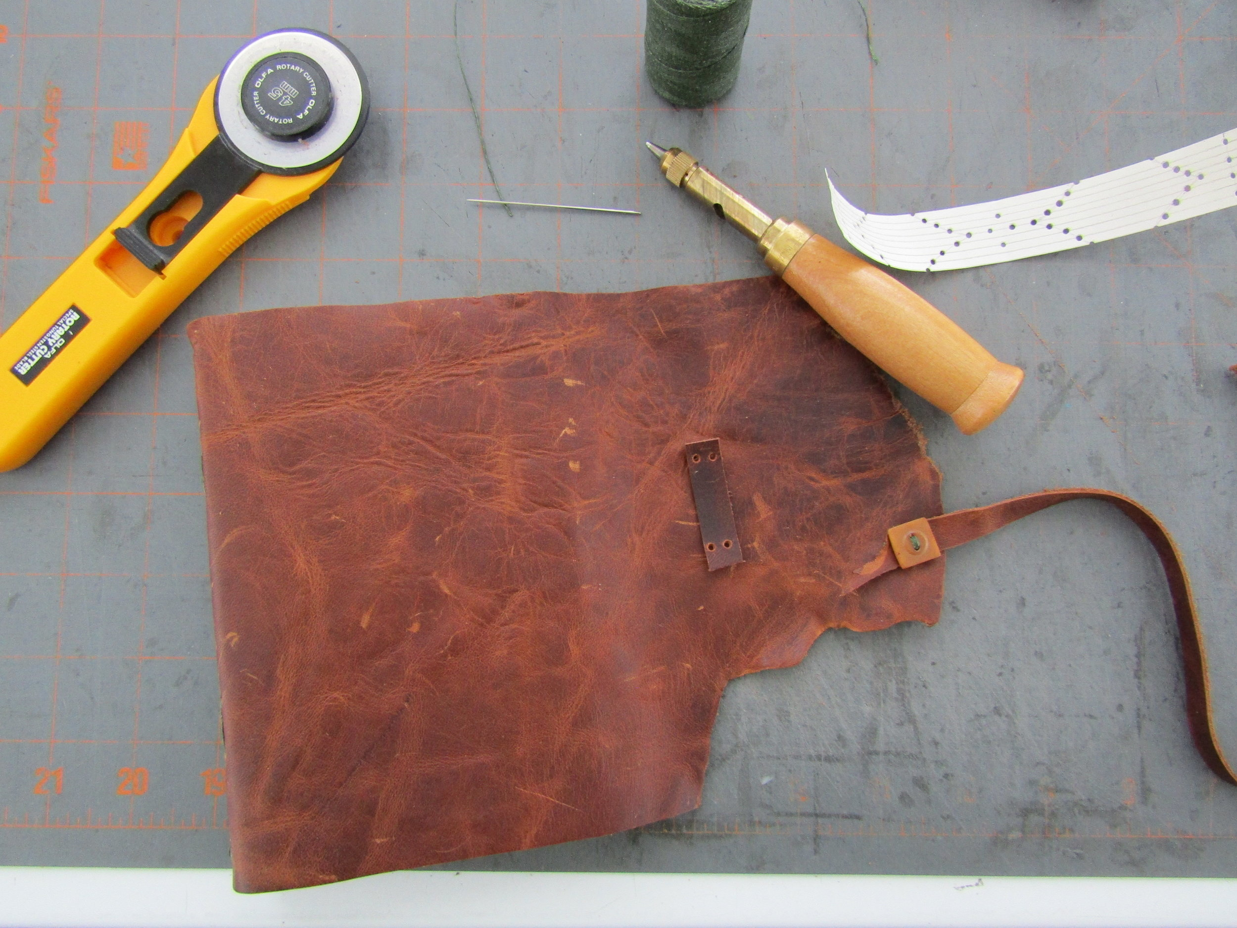 I kept the natural edge of this piece of  leather and used it on the book cover. Here I am figuring out and sewing the closure of the book.