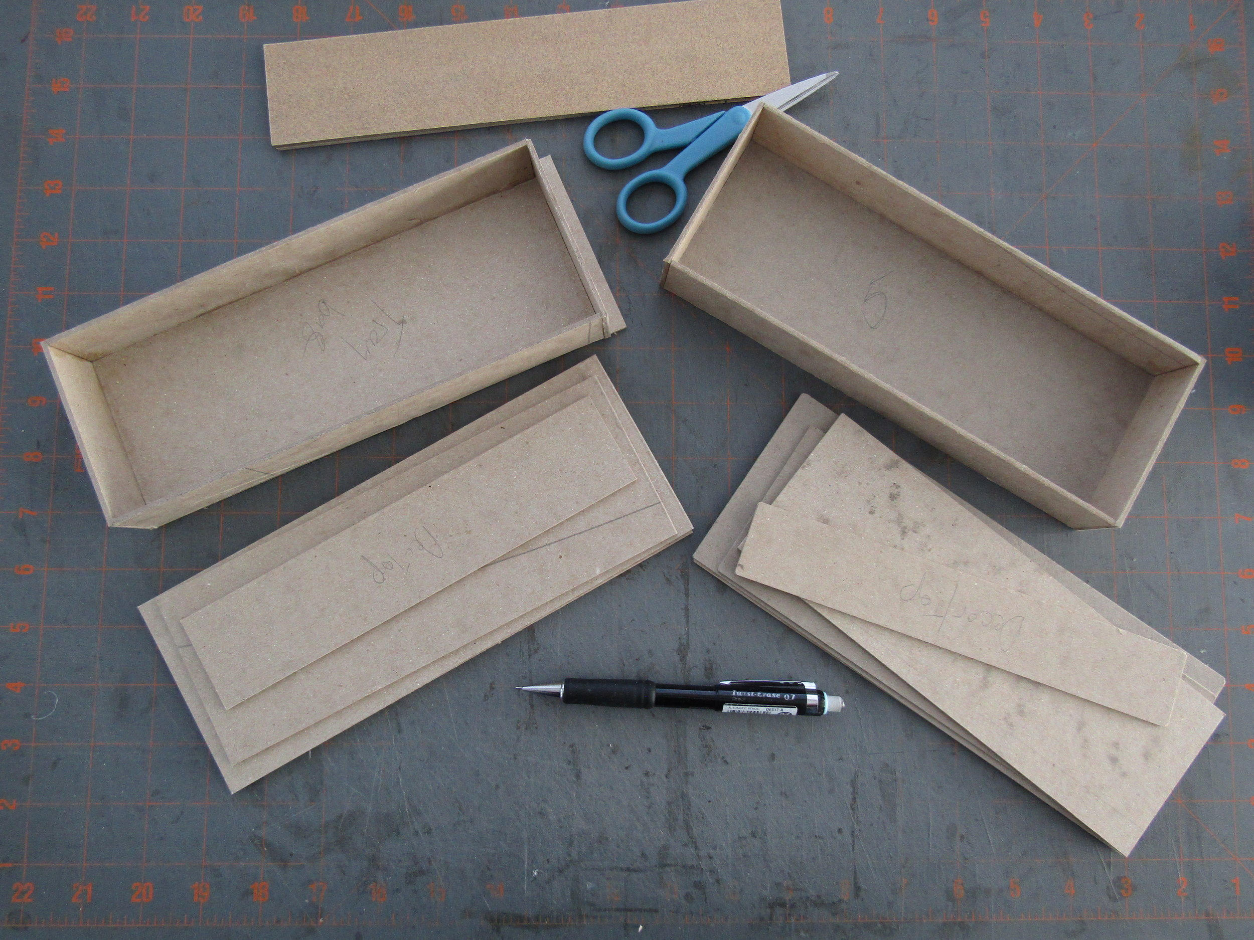 Davey board is cut into the various components. I assembled the trays using PVA. The flat pieces will be covered with papers and joined together to make the lids.