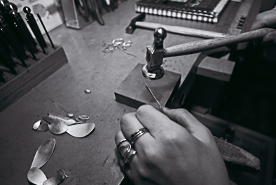 Sharon hammers on silver at her bench preparing to make a ring