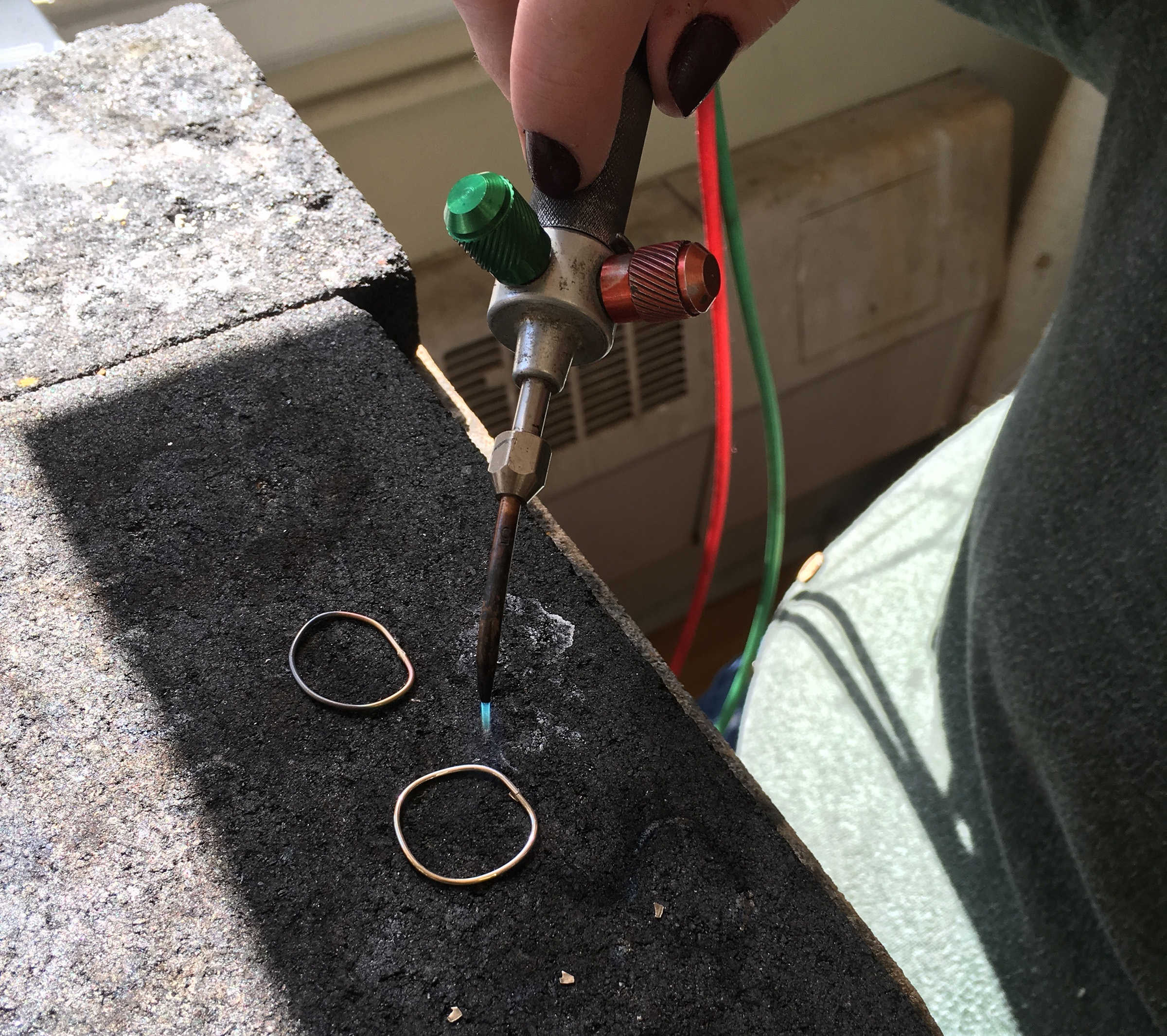 A student learns to use the torch to solder her stacking rings closed