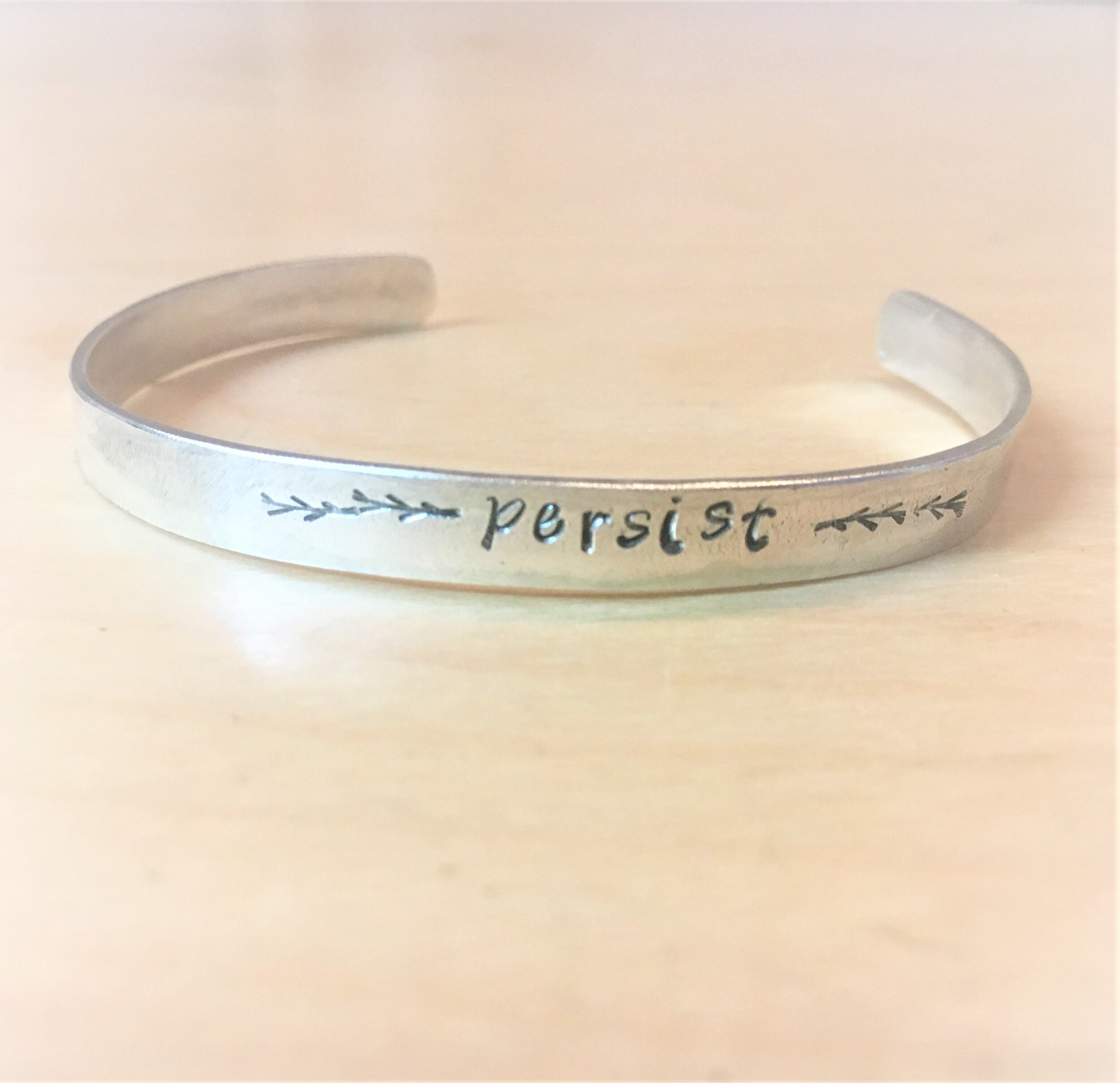 cuff bracelet with the word 'persist' stamped into it and some symbols of branches Bracelet is sterling silver