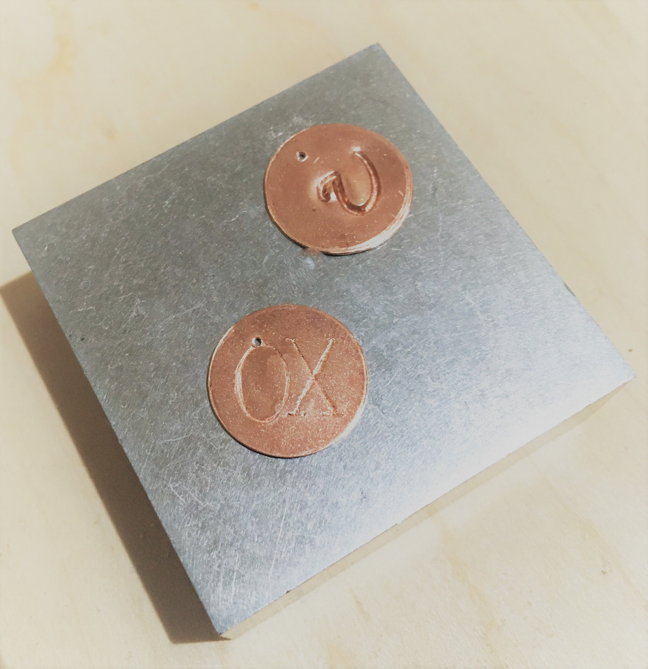 This image shows different fonts you'll get to choose from at this event.  This picture shows two copper tags on a steel block.