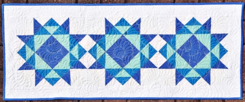 Three blocks set together without sashing and a small outer border makes a perfect table runner!