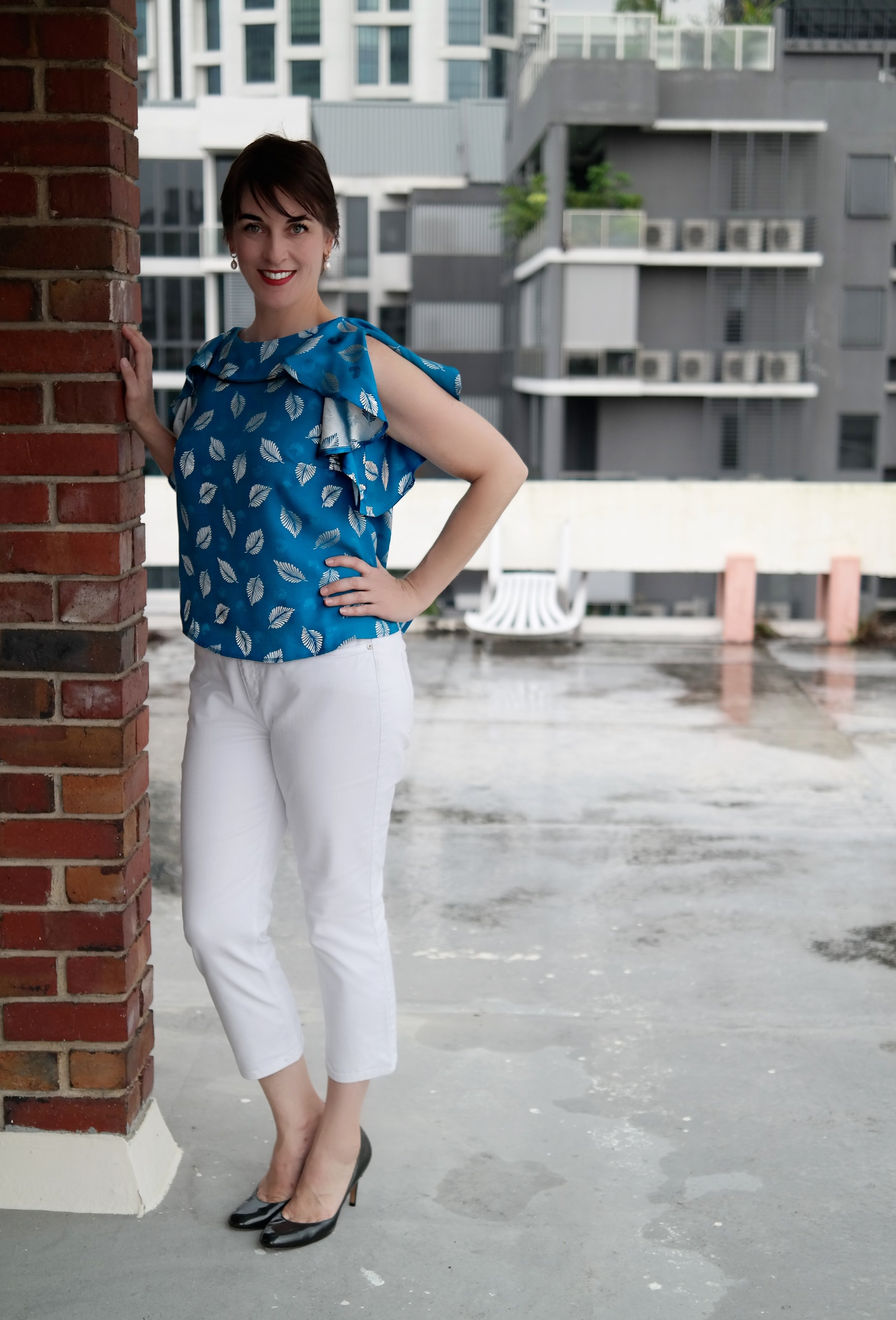 """Belinda Cooper - The pattern is beautifully drafted and the flounce design detail moves with you, and is flattering on almost any body shape. The Synthia is a great basic blouse with a twist. I used a double-sided viscose jacquard. I live in Singapore and find the most amazing fabric influenced by this region. The motif is a simple leaf design and the bright blue colour is typical of the Asian palette while the reverse is silver. I'm sure whoever sews this pattern will find they have a great top that can be worn for many years to come."""""""