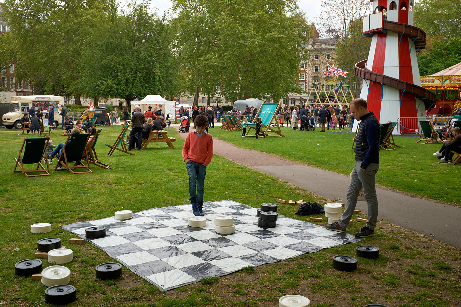Father and son enthusiastically challenge each other to a game of draughts.