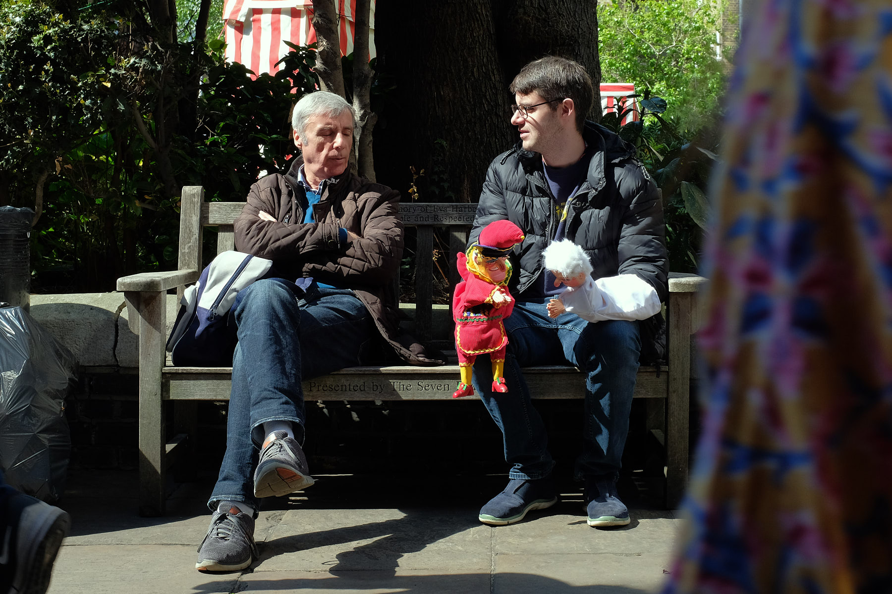 A father and son discuss puppets as they relax in the morning sun.